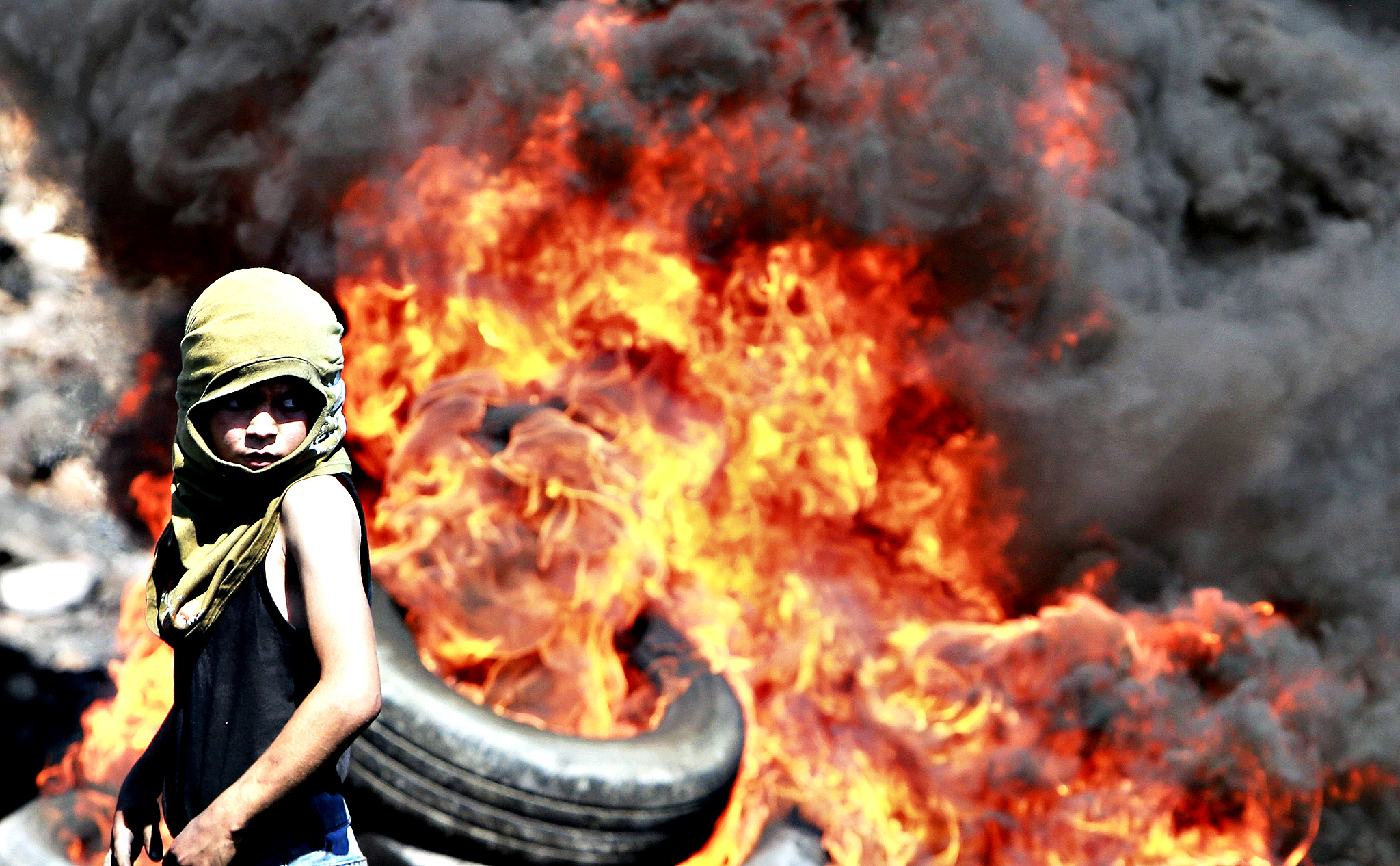 A Palestinian boy looks on near burning tyres during cashes with Israeli soldiers following a protest against the near-by Jewish settlement of Qadomem, in West Bank...A Palestinian boy looks on near burning tyres during cashes with Israeli soldiers following a protest against the near-by Jewish settlement of Qadomem, in the West Bank village of Kofr Qadom near Nablus September 19, 2014.