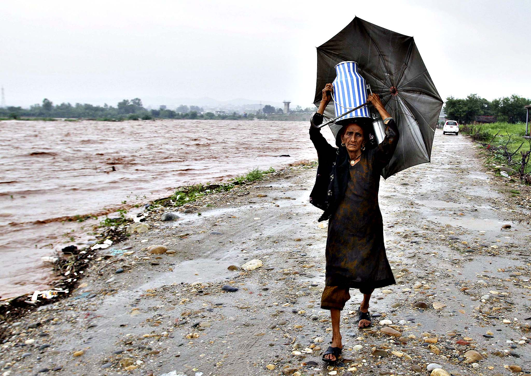 A nomadic woman carries a milk container while shifting her belongings to a safer place from the flooded banks of river Tawi after heavy rains in Jammu September 5, 2014. Sixty-five people were killed after heavy rains caused flash floods in Indian-administered Kashmir, including a wedding party on a bus that was swept away, officials said on Thursday. Authorities declared a disaster alert in the northern region after two days of heavy rain hit villages across the Kashmir valley, causing the worst flooding in two decades.