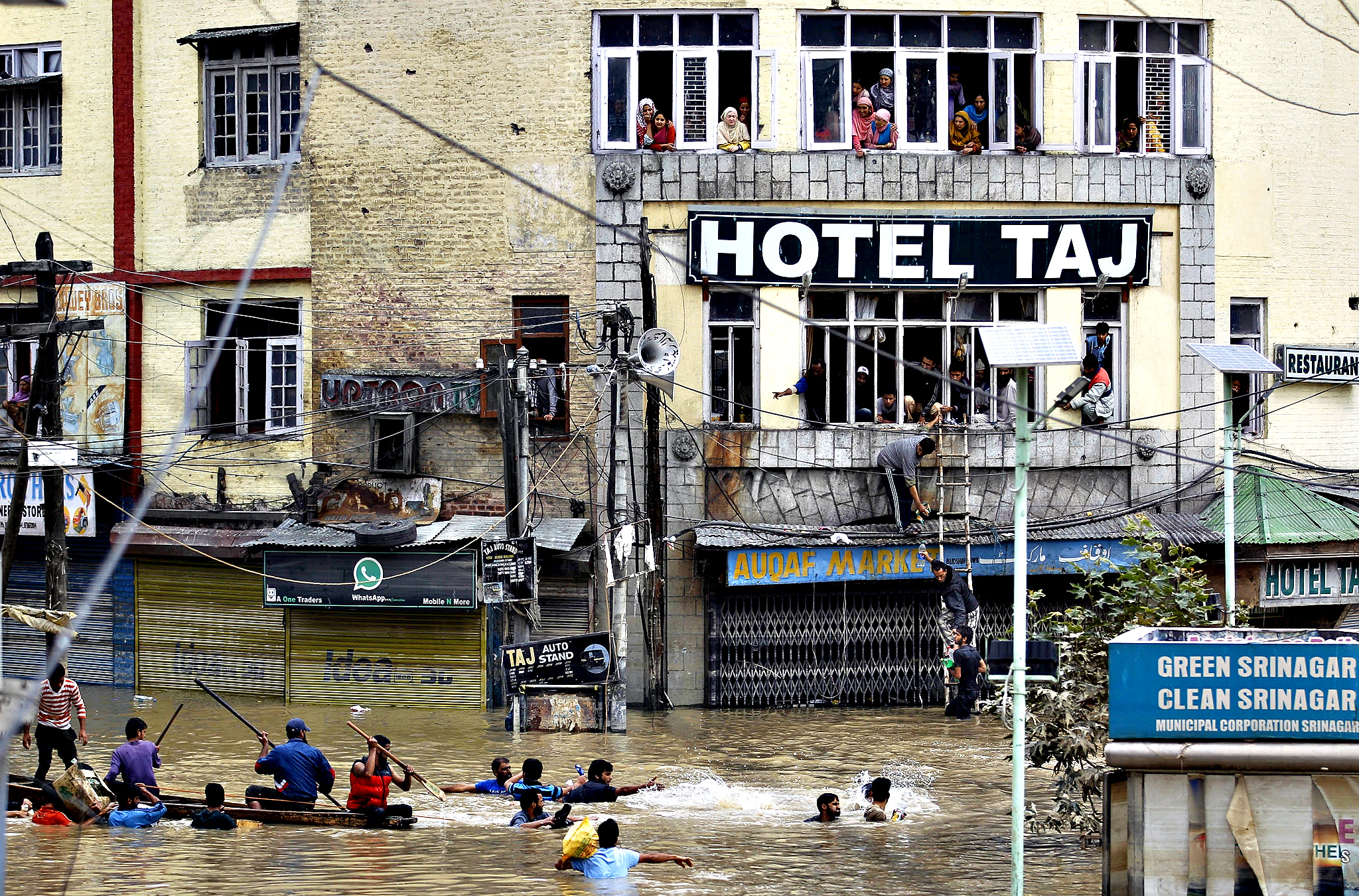 Flood victims watch from the windows of a hotel as Kashmiri volunteers try to get relief material across to them in the city center of Srinagar, India, Friday, Sept. 12, 2014.  Flash floods have killed hundreds, washed away crops, damaged tens of thousands of homes and affected over a million people since Sept. 3, when heavy monsoon rains lashed Pakistan's eastern Punjab province and the Kashmir region, claimed by both India and Pakistan.
