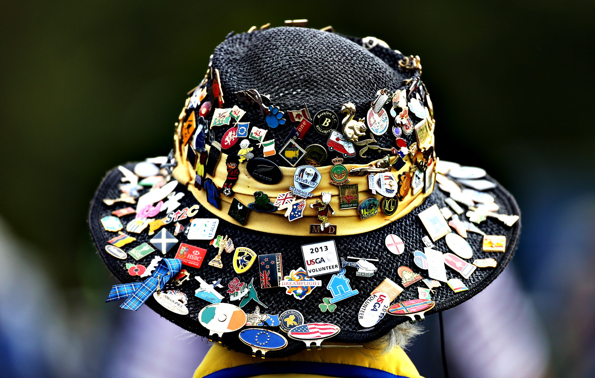 A spectator wearing a hat covered in badges waits for the opening ceremony of the 2014 Ryder Cup golf tournament, at Gleneagles, Scotland, Thursday, Sept. 25, 2014.