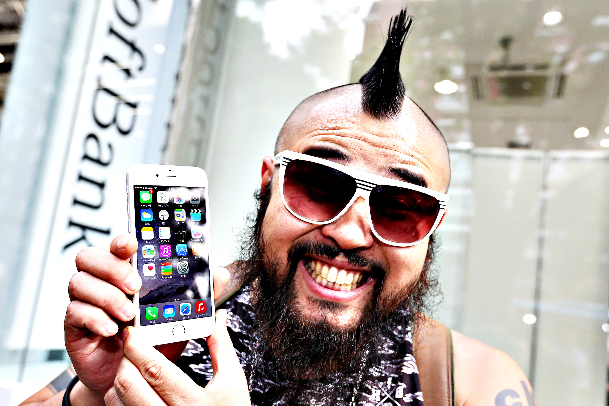 """Butch,"" the first customer at SoftBank Corp.'s Omotesando store displays his newly purchased Apple Inc. iPhone 6 for a photograph outside the store in Tokyo, Japan, on Friday, Sept. 19, 2014. Apple stores attracted long lines of shoppers for the debut of the latest iPhones, indicating healthy demand for the bigger-screen smartphones."