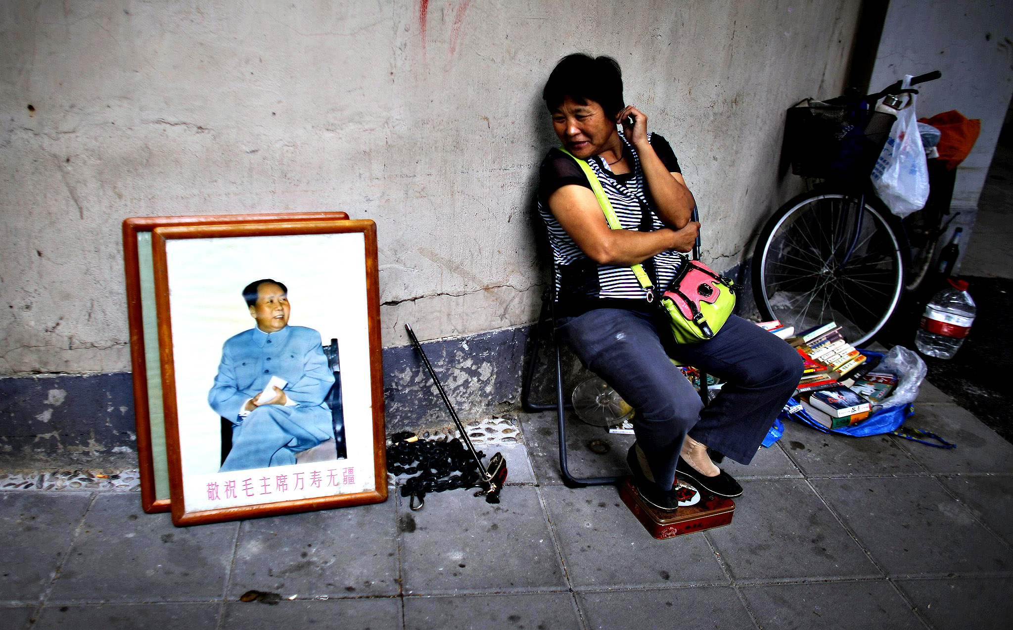 A woman sells a portrait of China's late chairman Mao Zedong at a busy street in Shanghai September 12, 2014.