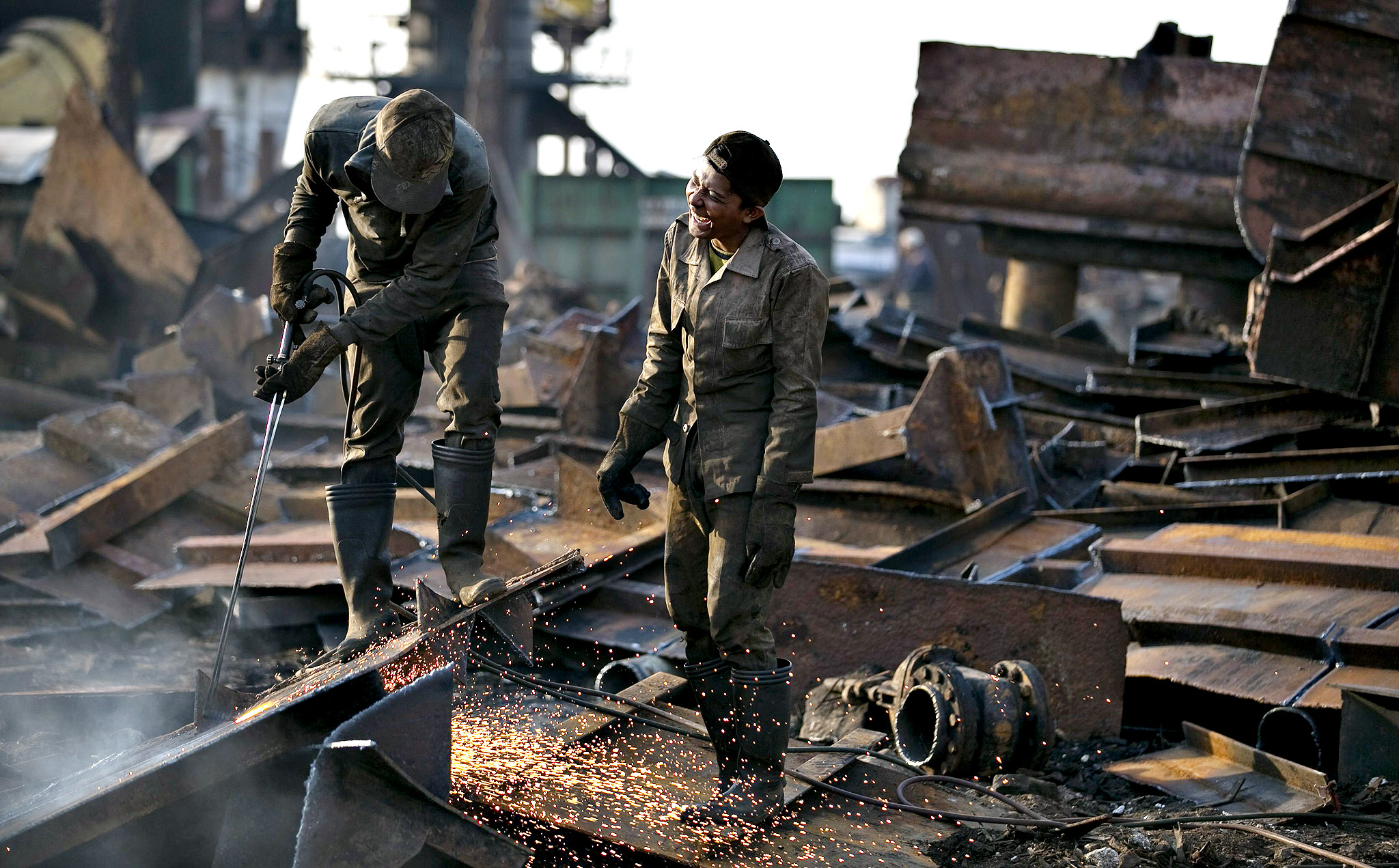 Workers chat while they break up part of an old ship for scrap metal near Tanjung Priok port, Indonesia's largest seaport, in Jakarta September 22, 2014.