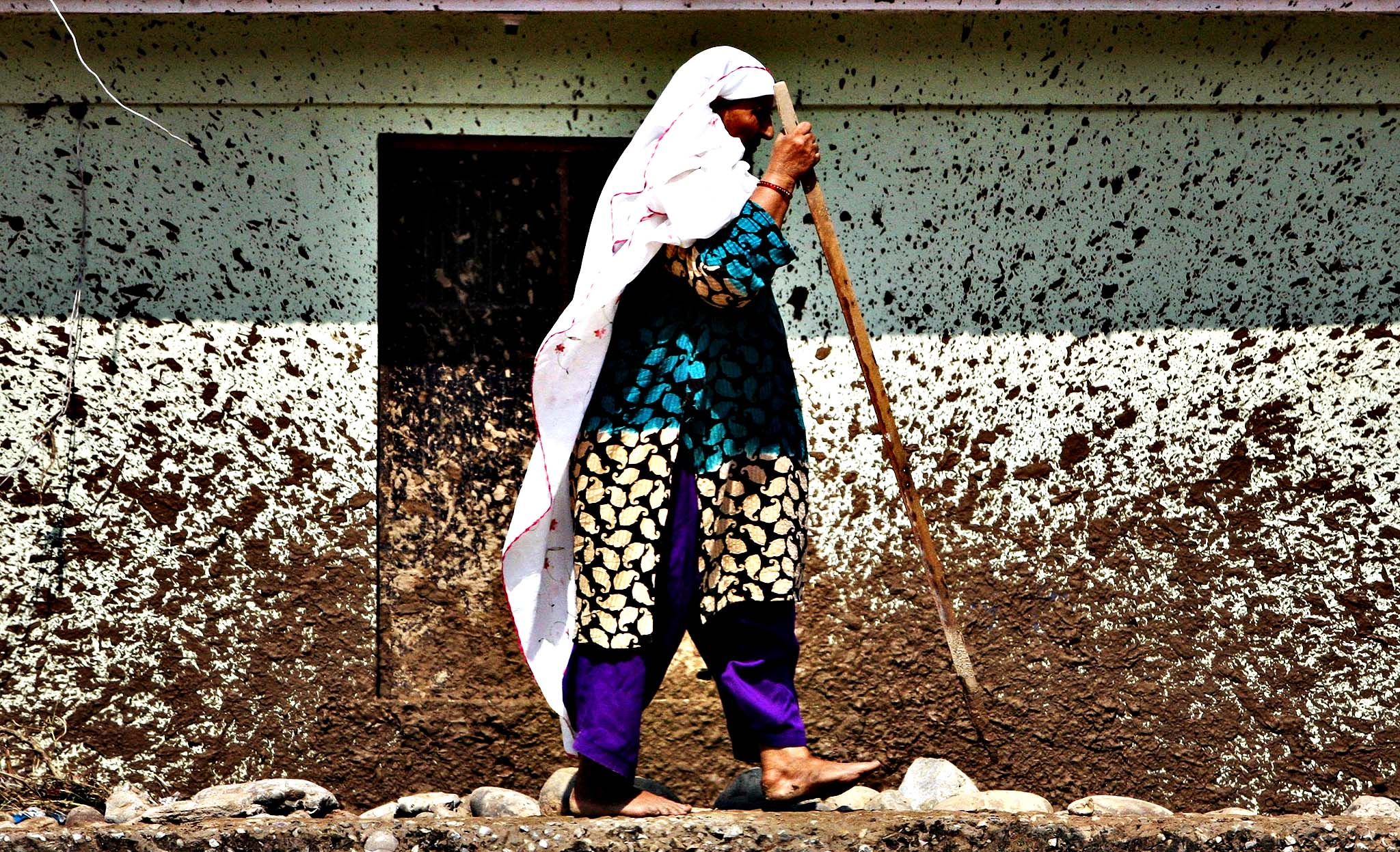 An Indian woman walks near her house that was damaged in floods on the banks of the Tawi River in Jammu, India, Monday, Sept. 8, 2014. Six days of rains in Indian Kashmir have left more than 120 people dead in the region's worst flooding in more than five decades, submerging hundreds of villages and triggering landslides, officials said.