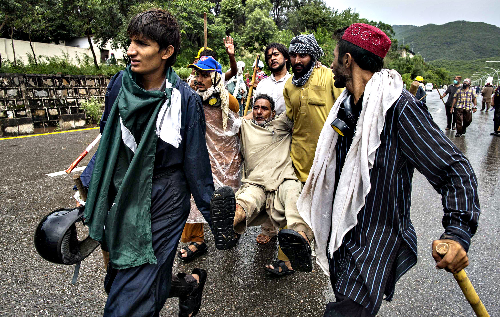 Supporters of Tahir ul-Qadri, a Sufi cleric and leader of Pakistan Awami Tehreek (PAT) party, help a fellow supporter who is injured, during the Revolution March in Islamabad September 1, 2014. Pakistani soldiers and paramilitary forces entered the headquarters of the state television channel PTV in Islamabad on Monday after a crowd of protesters stormed the building and took the channel off the air. Protesters led by opposition leaders Imran Khan, a hero cricket player turned politician, and ul-Qadri, a firebrand cleric, have been on the streets for weeks trying to bring down the government of Prime Minister Nawaz Sharif.