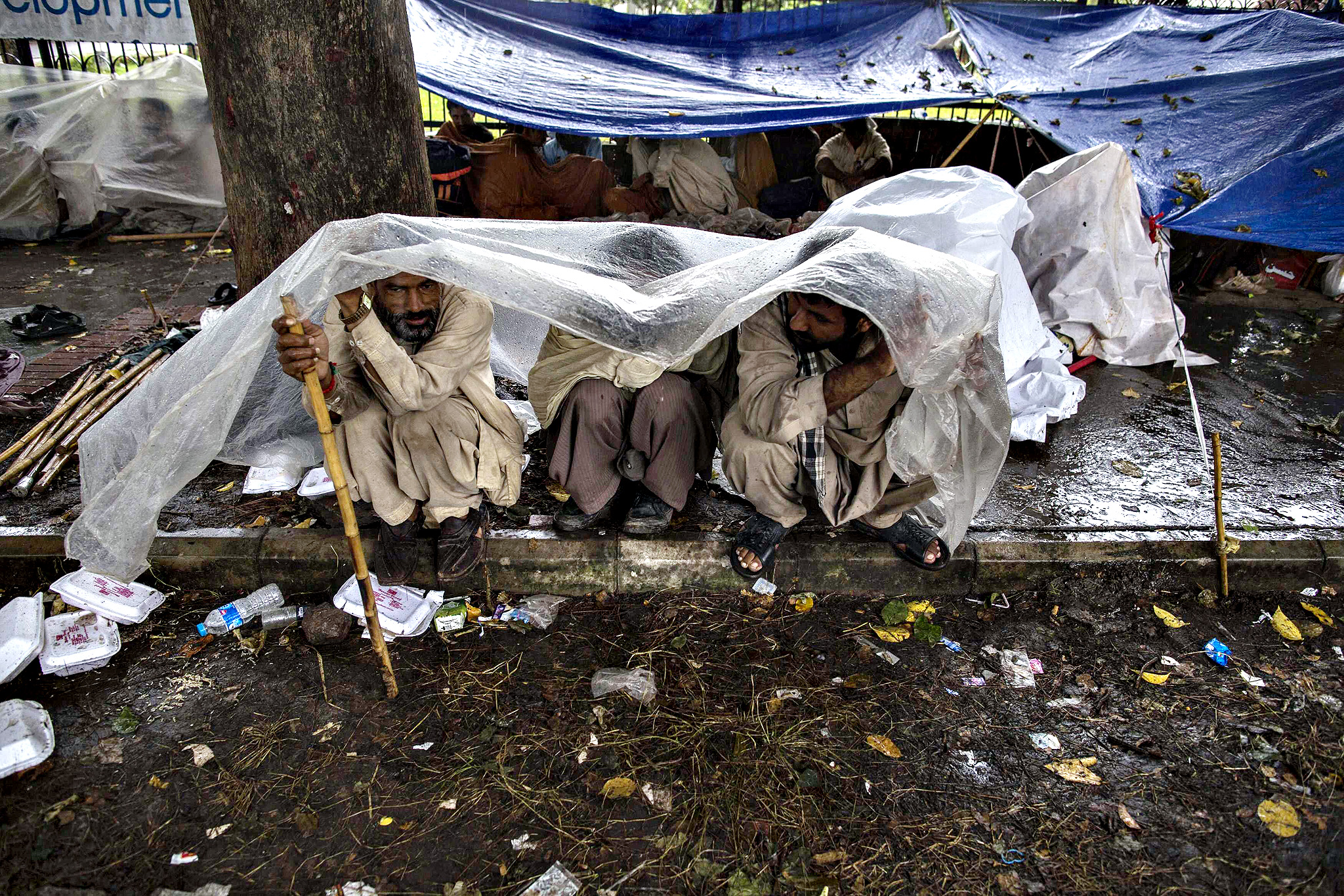 Anti-government protesters take shelter under plastic sheet during heavy rain in morning, in front of President's house in the Red Zone during the Revolution March in Islamabad...Anti-government protesters take shelter under a plastic sheet during heavy rain in the morning, in front of the President's house in the Red Zone during the Revolution March in Islamabad September 4, 2014. Pakistan's protest leaders demanding Prime Minister Nawaz Sharif's resignation prepared to resume talks with the government on Wednesday, reviving hopes for a negotiated solution to a crisis that has shaken the coup-prone nation.