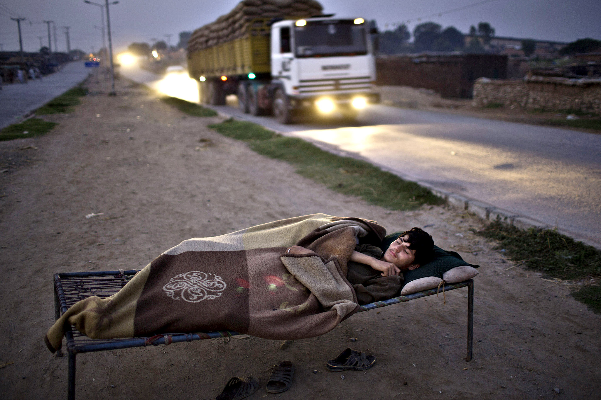 A Pakistani youth, who was Internally Displaced from Pakistan's tribal areas, sleeps on a bed to escape the heat trapped in his mud home, near a wholesale fruit and vegetable market where he works, on the outskirts of Islamabad, Pakistan, early Monday, Sept. 22, 2014.