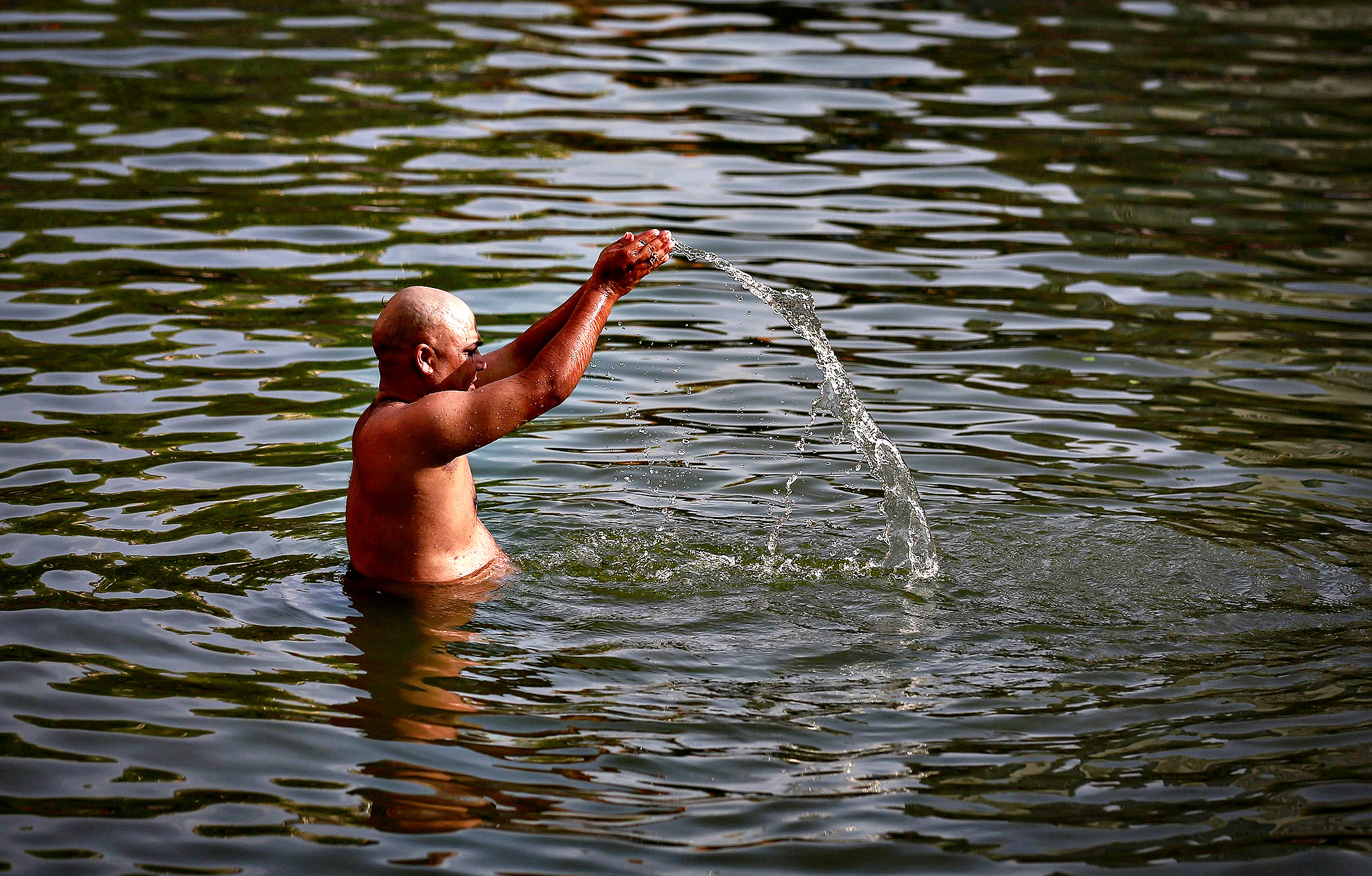 "A Hindu devotee prays in a holy pond on the auspicious day of ""Mahalaya"" in Mumbai on Wednesday. Hindus offer prayers with holy water after taking a dip in the river to honour the souls of their departed ancestors during Mahalaya, which is also called 'Shraadh' or Pitra Paksha."
