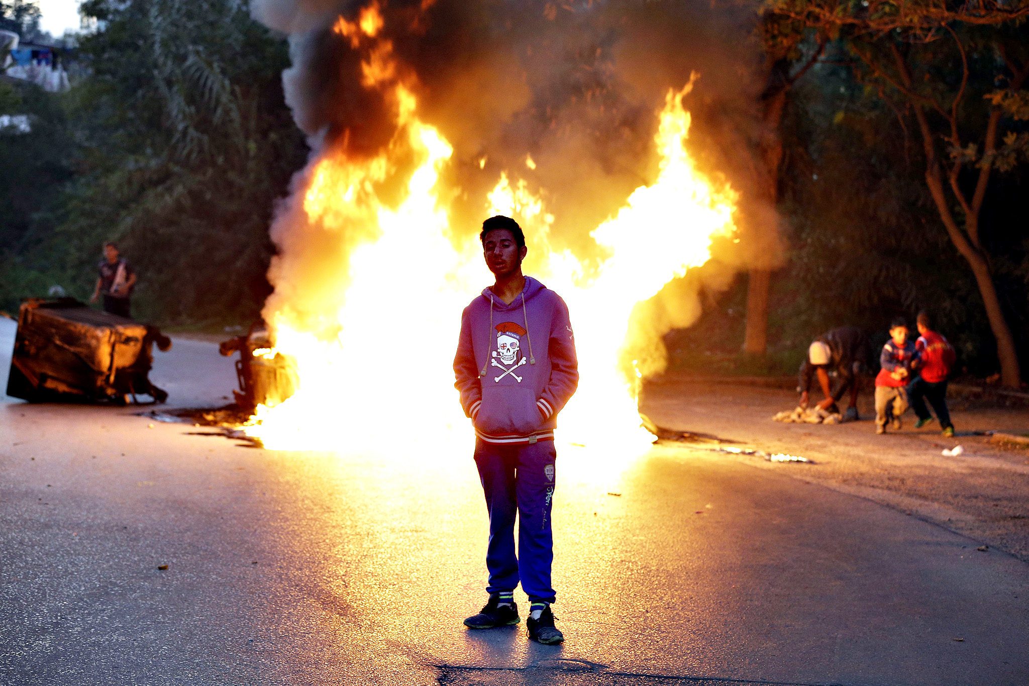 A young Roma man stands next to a burning barricade during a protest in Athens on Tuesday, Sept. 30, 2014.  The Greek Roma community, protesting authorities' plans to demolish their illegal settlement and move them to a remote spot in the countryside, blocked a main northern Athens avenue for hours Tuesday, using rubbish bins that they then set on fire. Eventually, a compromise was reached whereby a few uninhabited shacks will be knocked down, and the rest will stay in place pending a final agreement on relocating the Roma.