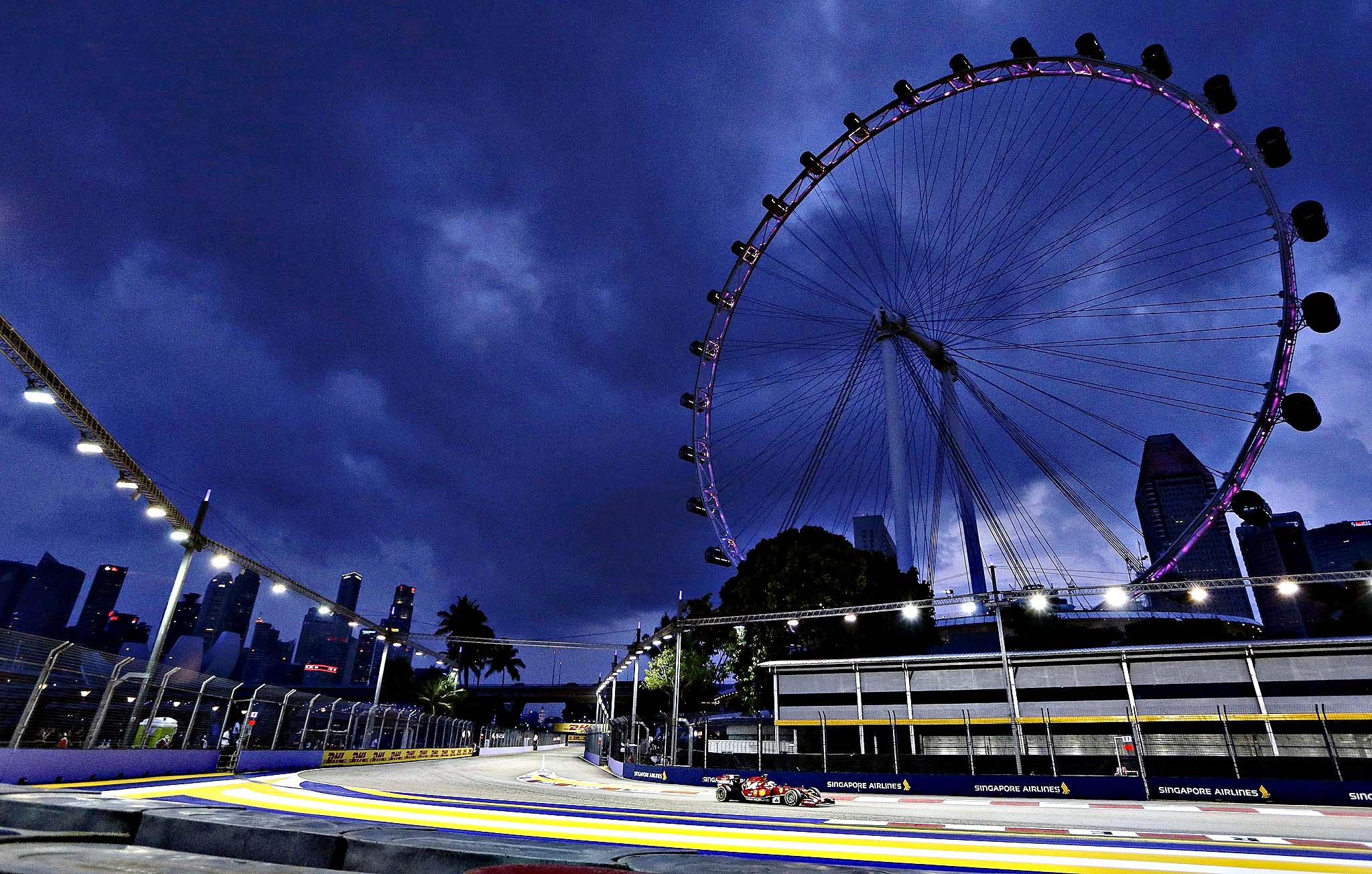 Ferrari Formula One driver Alonso of Spain drives past the Singapore Flyer observation wheel during the first practice session of the Singapore F1 Grand Prix...Ferrari Formula One driver Fernando Alonso of Spain drives past the Singapore Flyer observation wheel during the first practice session of the Singapore F1 Grand Prix on the Marina Bay street circuit in Singapore September 19, 2014.