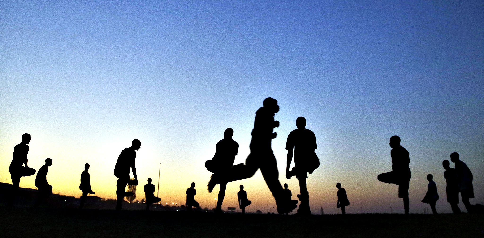 Young boys warm up before playing soccer on a dusty field in Soweto, South Africa