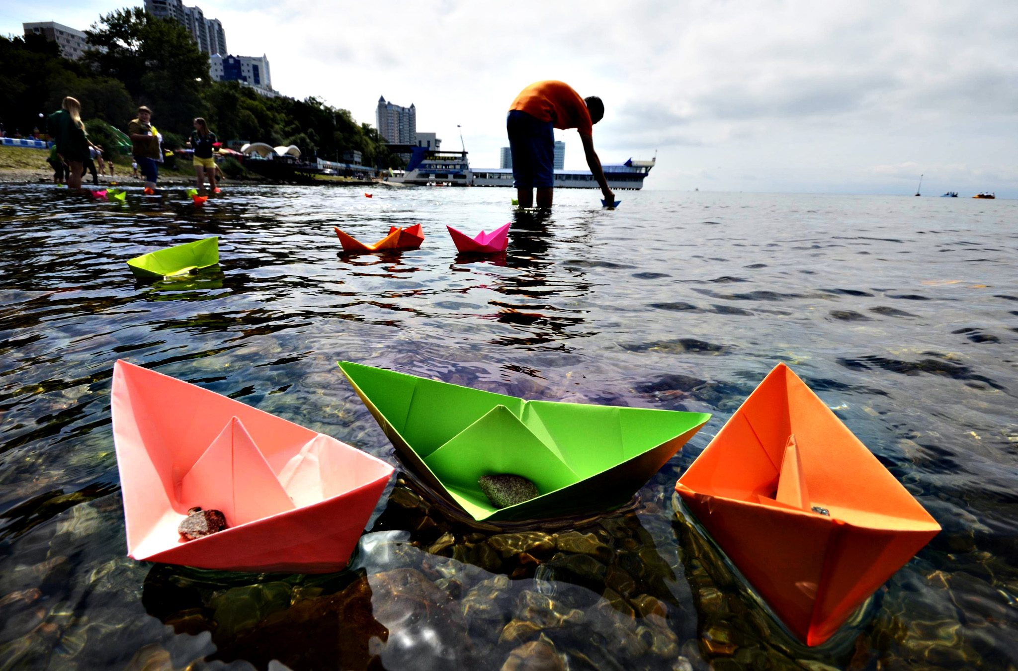 Residents launch paper boats during celebrations for the 69th anniversary of the end of World War Two in the far eastern city of Vladivostok, September 2, 2014. The holiday, marking the victory over Japan in World War II, is a Russian national memorial day, established by then President Dmitry Medvedev and approved by the Russian State Duma and the Federation Council on July 23, 2010.