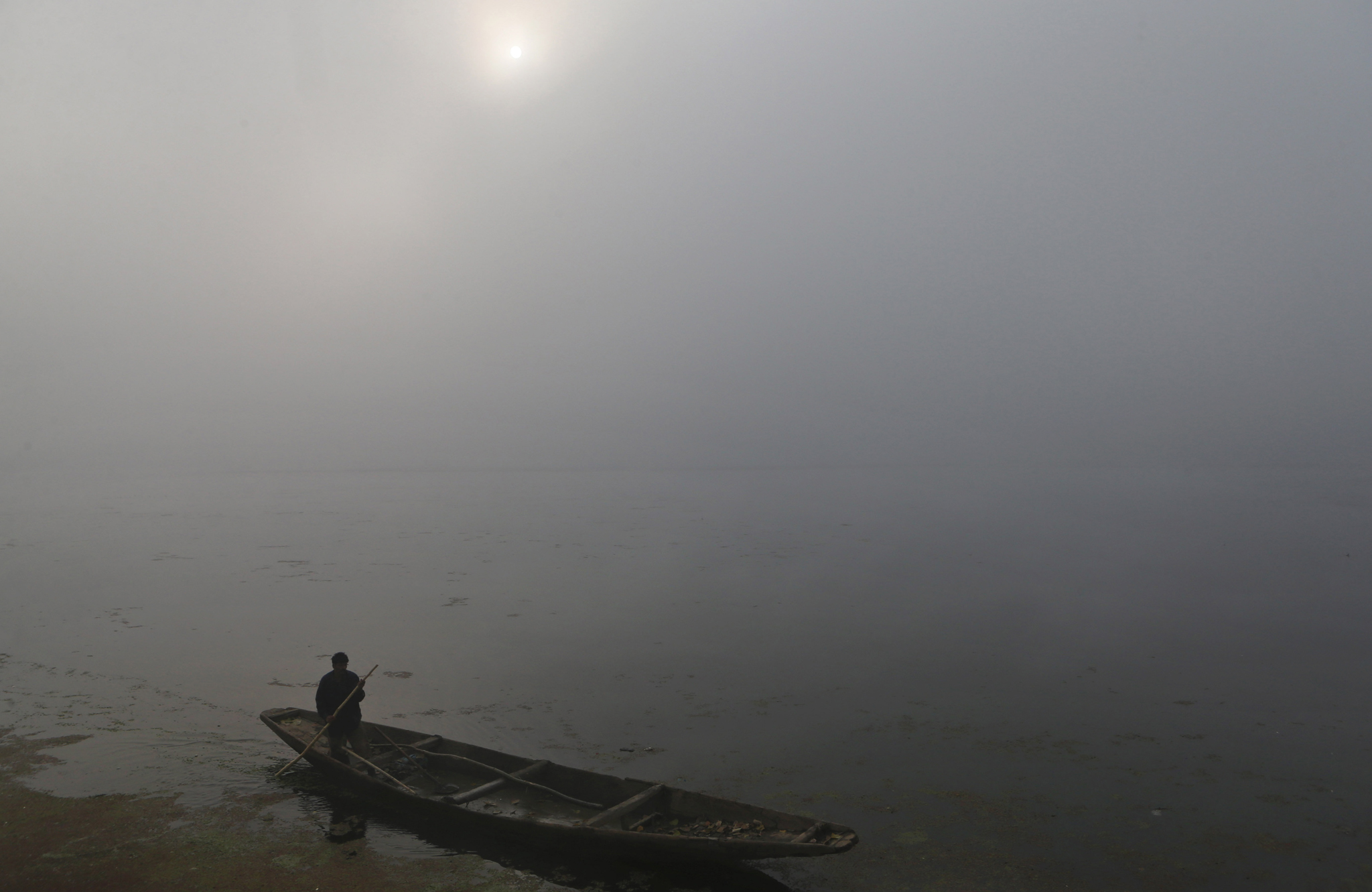 A Kashmiri boatman rows his boat on the Dal Lake surrounded by dense fog on a cold morning in Srinagar, India, Thursday, Oct. 30, 2014. Fog disrupts normal life in most parts of northern India during the winter months. (AP Photo/Dar Yasin)