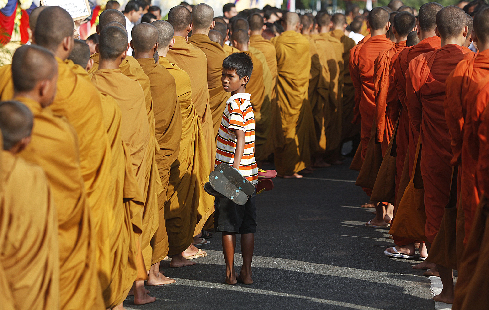 A boy carries shoes as Buddhist monks walk in front of the Royal Palace during a ceremony to mark the 10th anniversary of King Norodom Sihamoni coronation, in Phnom Penh...A boy carries shoes as Buddhist monks walk in front of the Royal Palace during a ceremony to mark the 10th anniversary of King Norodom Sihamoni coronation, in Phnom Penh October 28, 2014. Cambodians mark the 10th anniversary of Sihamoni's coronation from October 28-29. REUTERS/Samrang Pring (CAMBODIA - Tags: RELIGION ROYALS ANNIVERSARY SOCIETY)