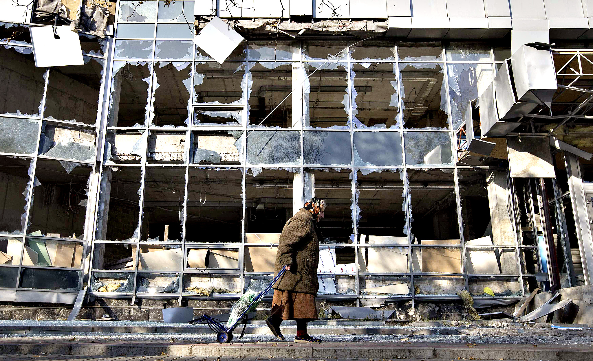 A woman pulls her shopping trolley as she walks past a building that was damaged by shelling in Donetsk, eastern Ukraine, October 15, 2014.