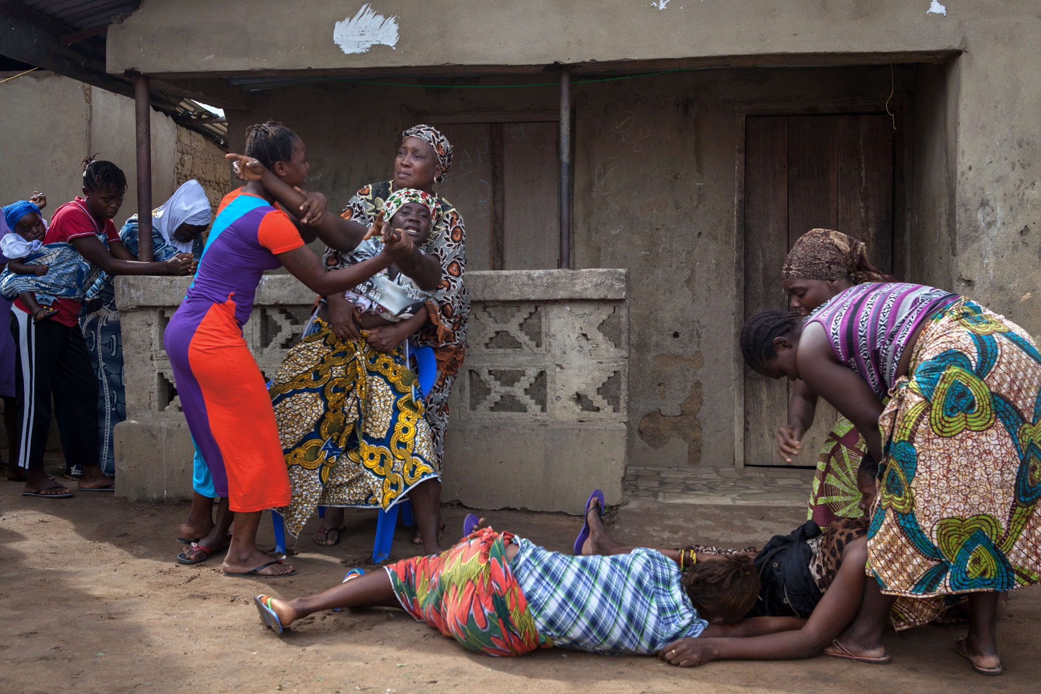 Women faint (Bottom) as another reacts while volunteers (unseen) take away from a nearby house the body of a woman who died of Ebola, in Waterloo, some 30 kilometers southeast of Freetown, on October 7, 2014. Dozens of British military personnel are due to fly to Sierra Leone next week to help build medical facilities to combat the Ebola epidemic, the defence ministry said on October 7.  AFP PHOTO / FLORIAN PLAUCHEURFLORIAN PLAUCHEUR/AFP/Getty Images