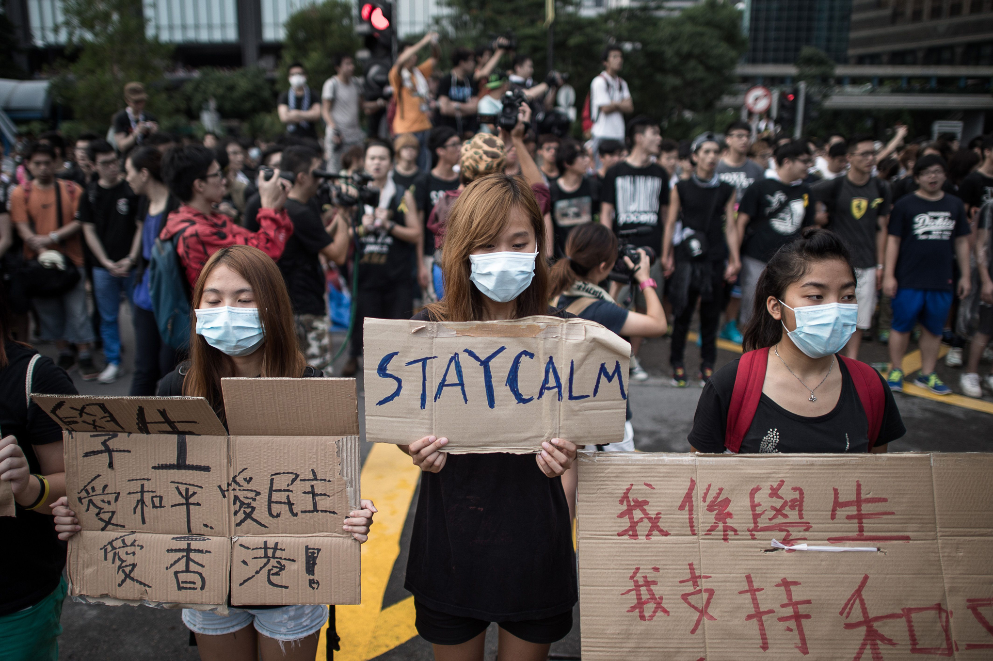 Pro-democracy demonstrators display placards as they gather near a ceremony marking China's 65th National Day in Hong Kong on October 1, 2014. Hong Kong protesters who braved thunderstorms to stage their third night of pro-democracy rallies began massing on October 1 at the city's Golden Bauhinia Square as China's National Day holiday lent their campaign for free elections fresh momentum.