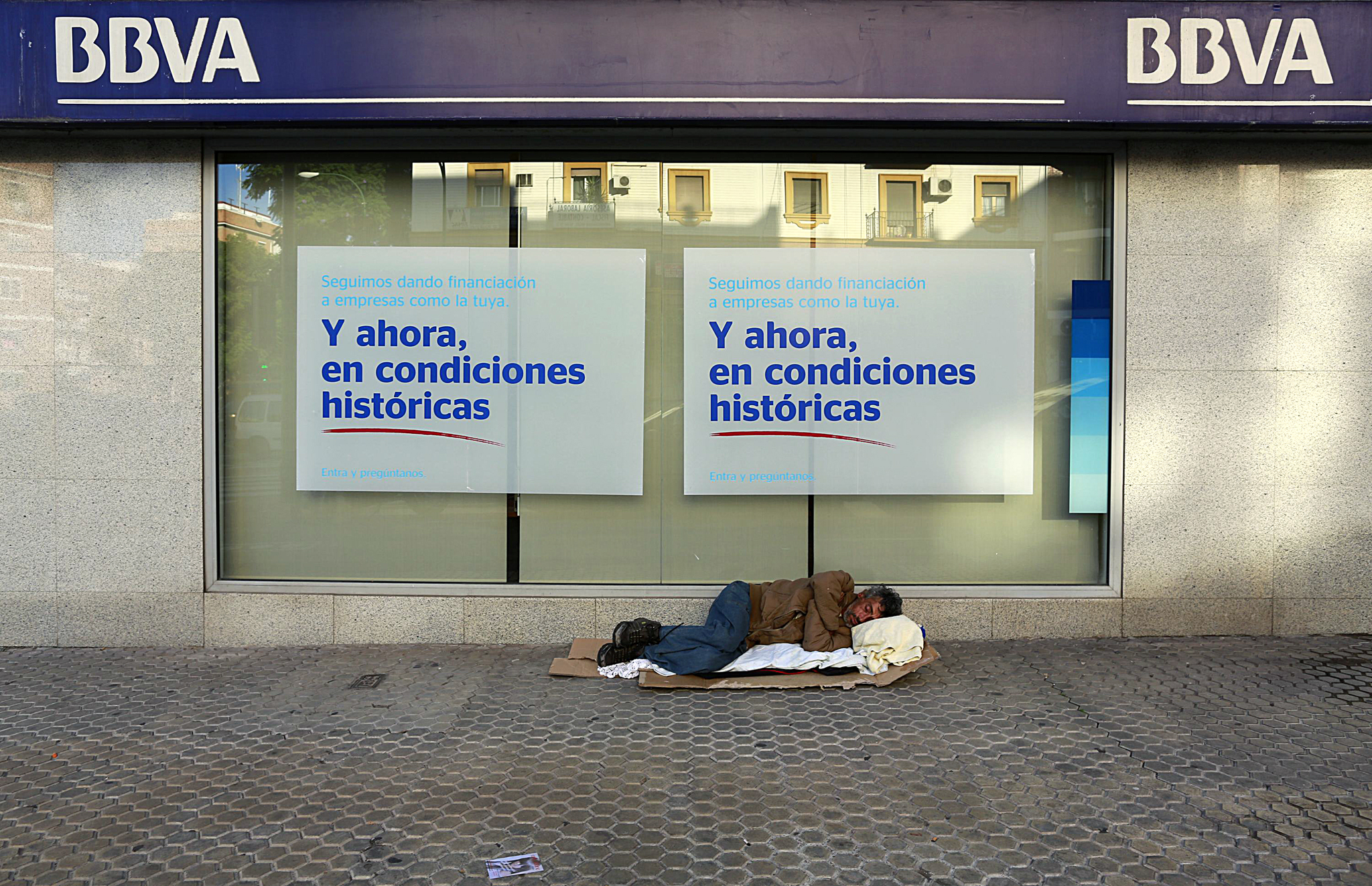 "A homeless man sleeps on the pavement outside a BBVA bank branch in the Andalusian capital of Seville...A homeless man sleeps on the pavement outside a BBVA bank branch in the Andalusian capital of Seville, southern Spain October 30, 2014. The advertisement poster reads ""We continue to provide financing to companies like yours. And now, in historical terms. Come in and ask.""  REUTERS/Marcelo del Pozo (SPAIN - Tags: SOCIETY BUSINESS)"