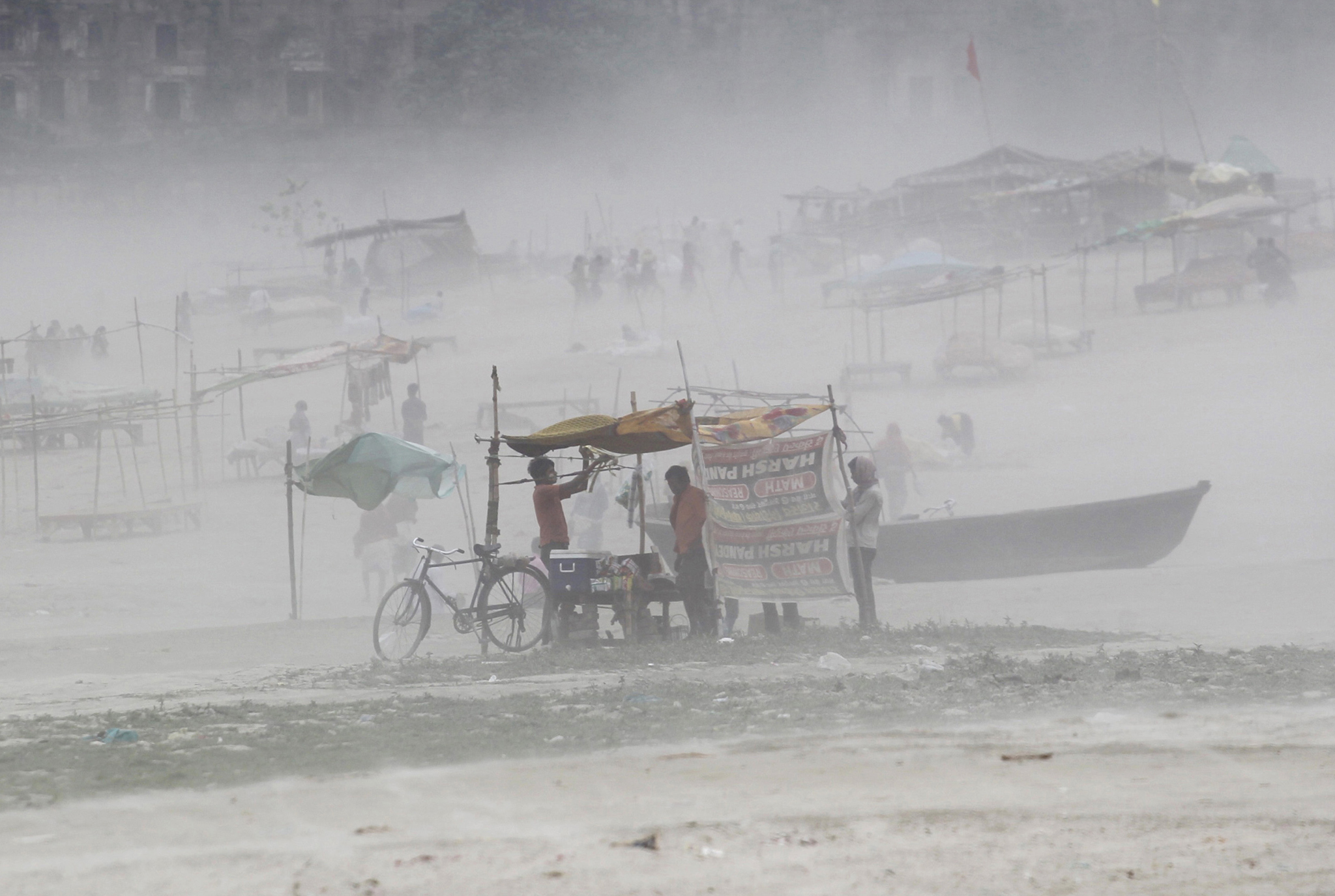 A man fixes tarpaulin on his stall during a dust storm on the banks of the river Ganges in the northern Indian city of Allahabad October 13, 2014.