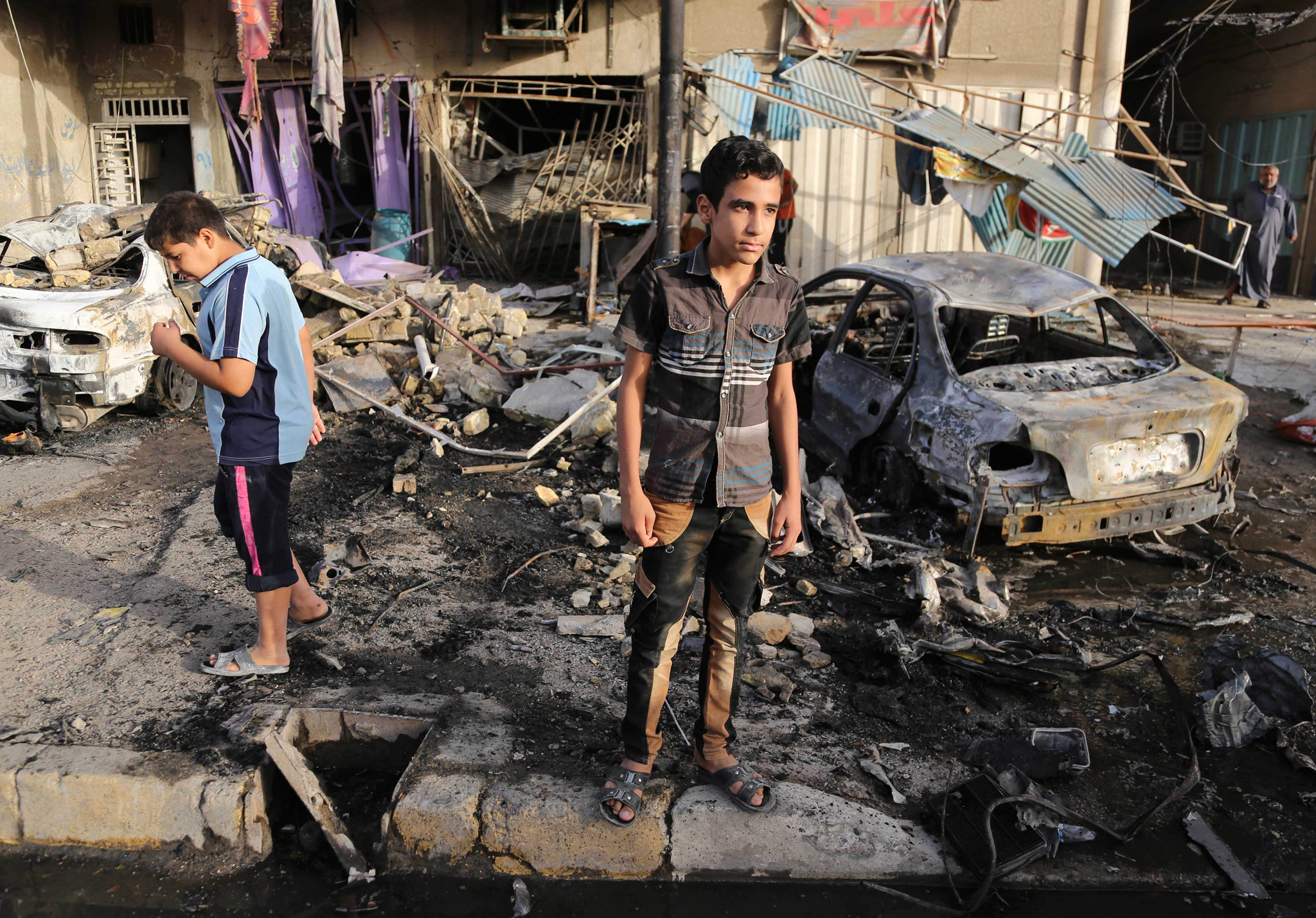 Boys inspect the site of double car bombings in the northern Shiite district al-Hurriyah in Baghdad, Iraq, Wednesday, Oct. 1, 2014. On Tuesday, officials say a wave of bombings targeted commercial areas across Iraq, killing and wounding dozens of people. (AP Photo/Karim Kadim)