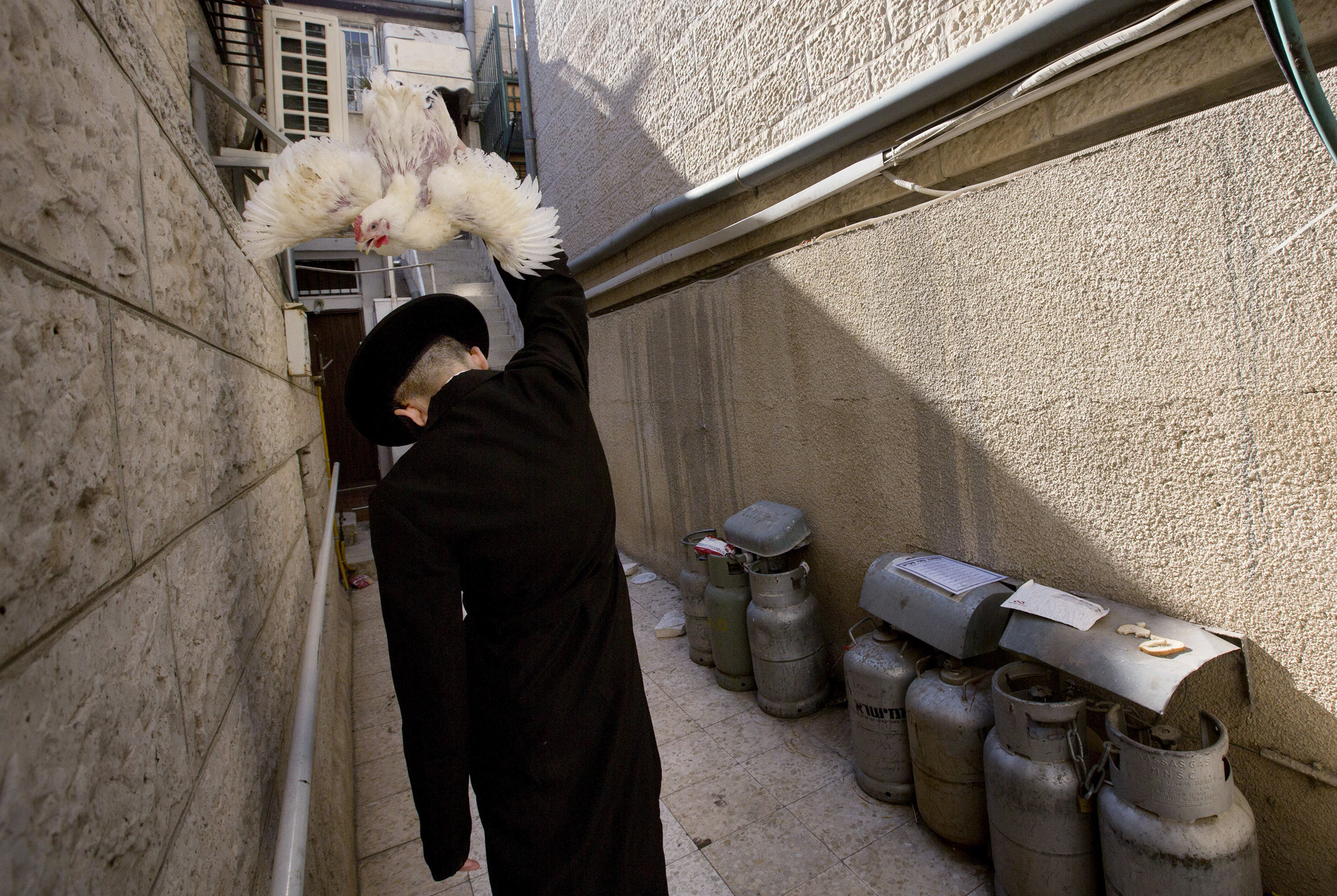 An ultra-Orthodox Jewish man swings a chicken over his head as part of the Kaparot ritual in Jerusalem,