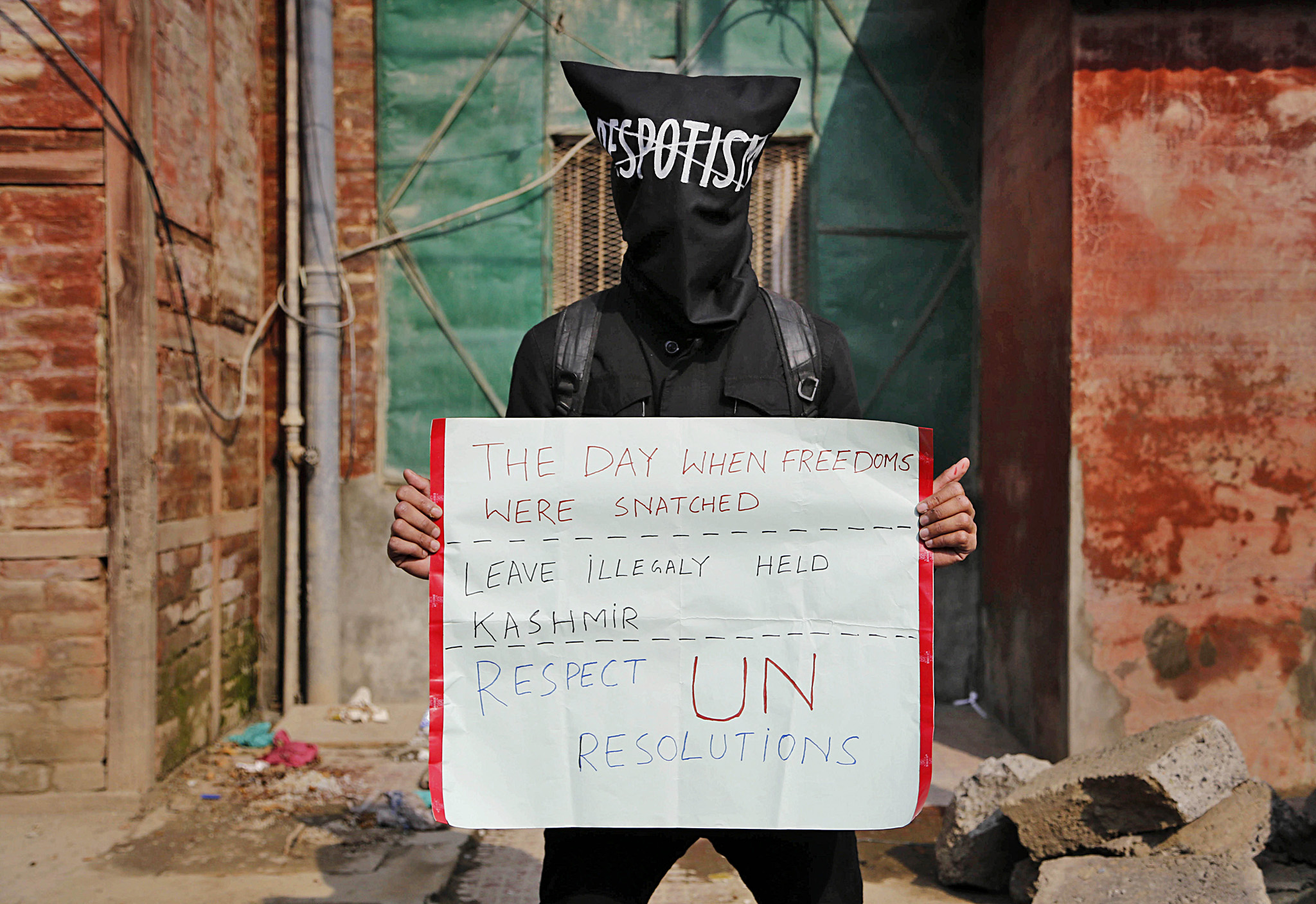 A masked Kashmiri protester stands with a placard during a protest in Srinagar, India, Monday, Oct. 27, 2014. Separatists groups in Kashmir called a general strike Monday to mark the anniversary of the day Indian troops took control of the region in 1947. (AP Photo/Mukhtar Khan)