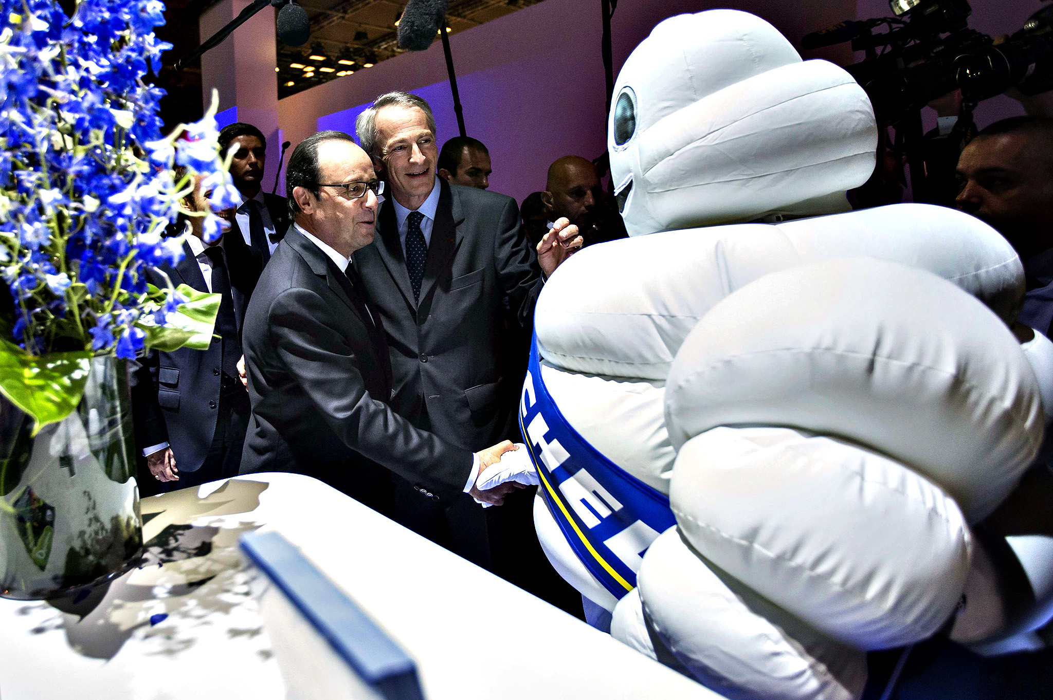 French President Francois Hollande (L) is greeted by President of tire company Michelin, Jean-Dominque Senard (C) and a person dressed in a Michelin-Man costume during an official visit to the Paris Motor Show in Paris on October 03, 2014. The Paris Motor Show, which takes place every two years, runs from October 4 to 19, 2014 with international car makers presenting their latest models and studies.