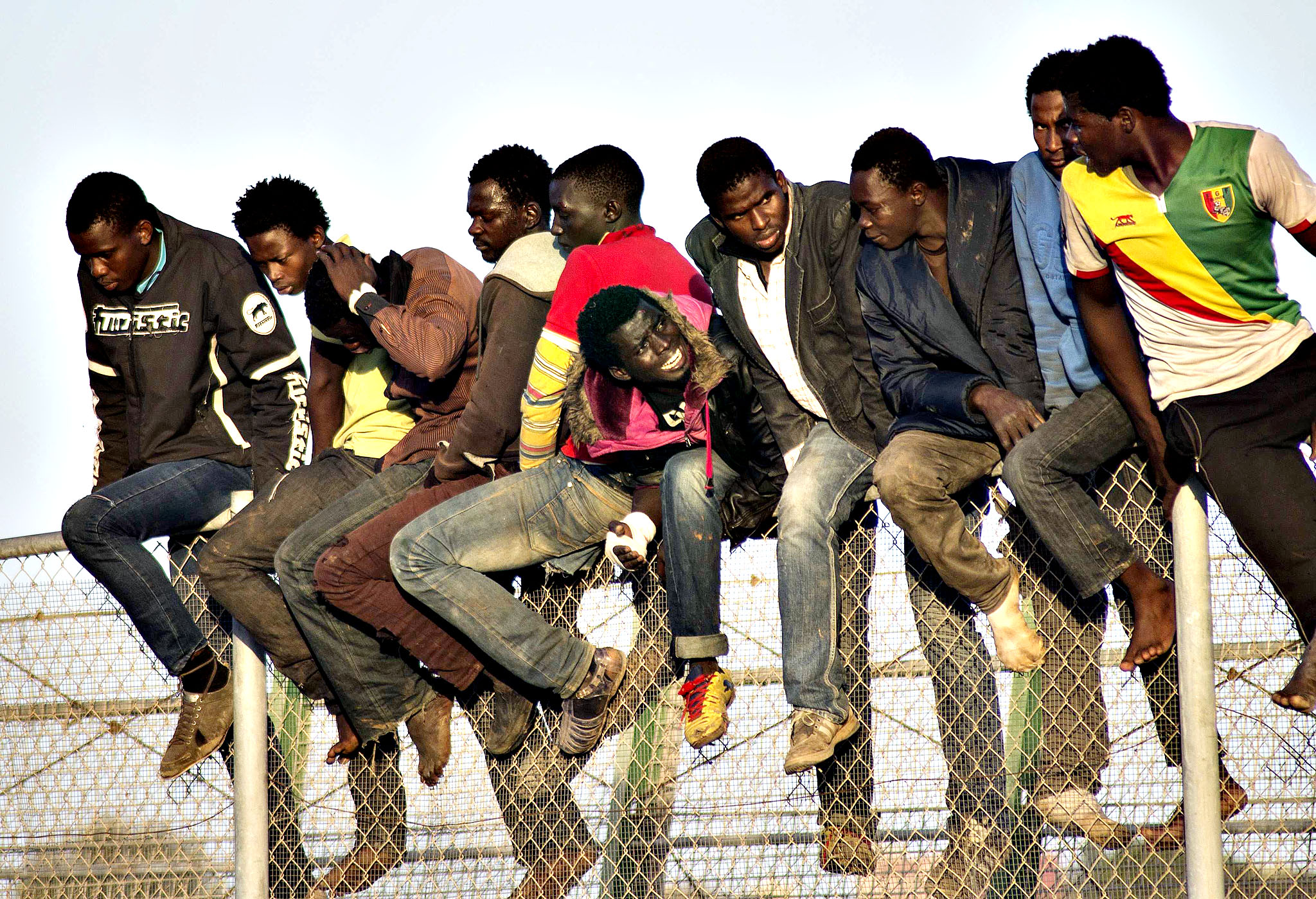 African migrants sit atop a border fence during an attempt to cross into Spanish territories, between Morocco and Spain's north African enclave of Melilla October 22, 2014. Around 400 migrants attempted to cross the border into Spain, according to local media.