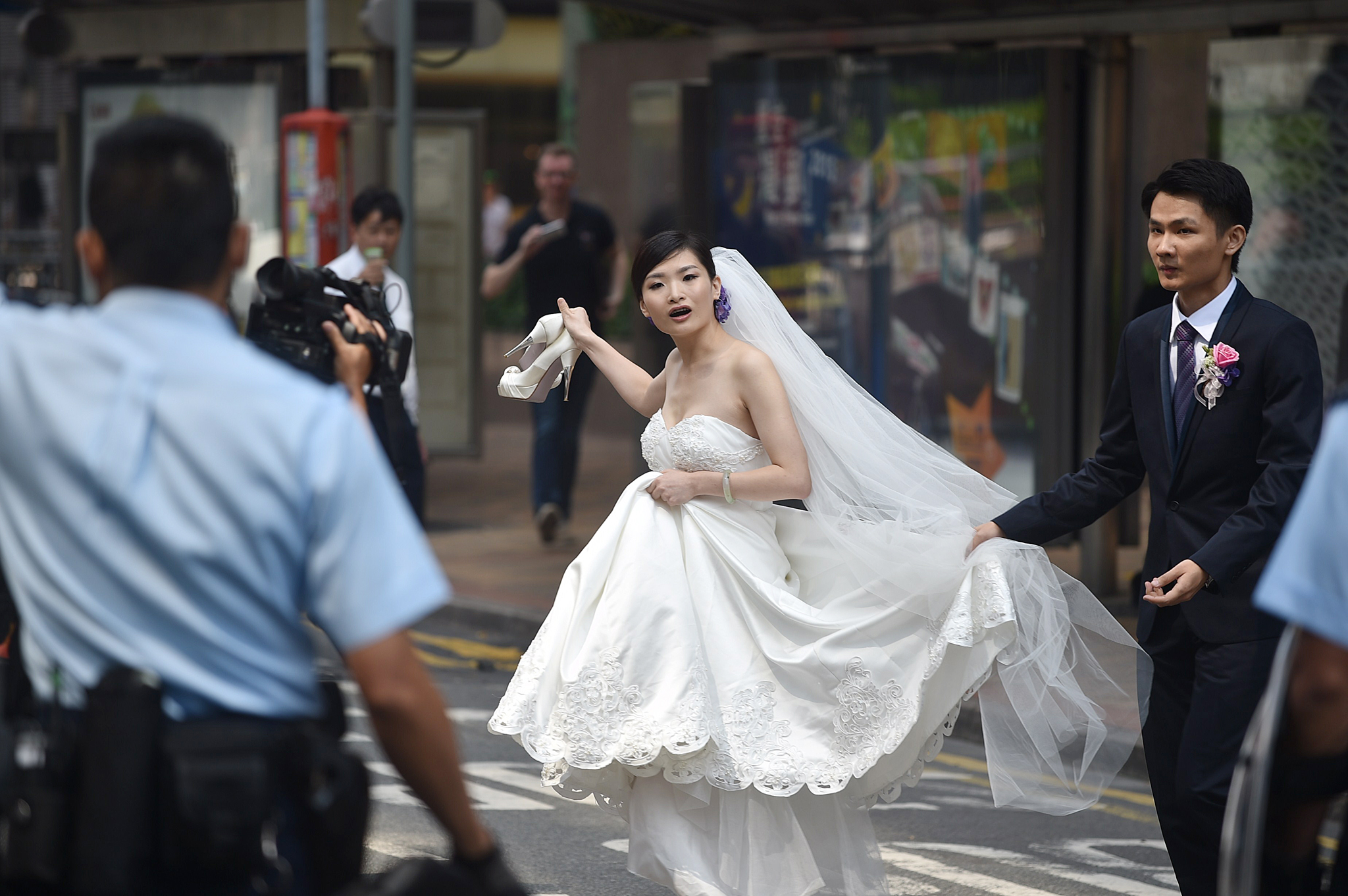 A wedding couple speak to police officer...A wedding couple speak to police officers as they try to leave the area of a pro-democracy protest in the Admiralty district of Hong Kong on October 14, 2014.  Dozens of police removed barricades from a second Hong Kong protest site,  a day after a similar attempt at the city's main occupied area largely backfired as demonstrators rebuilt and reinforced their defences.  AFP PHOTO/Pedro UgartePEDRO UGARTE/AFP/Getty Images