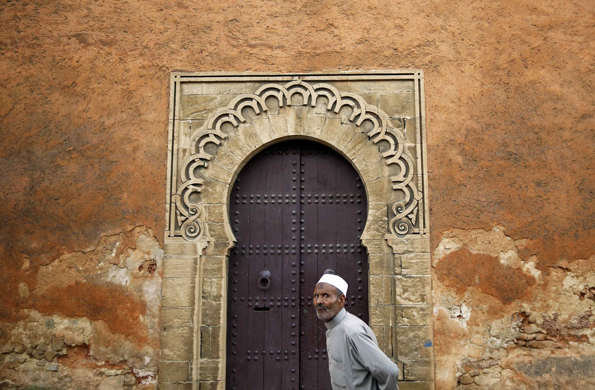 "A man walks in front of doors in a wall of Rabat's Medina...A man walks in front of doors in a wall of Rabat's Medina September 23, 2014. UNESCO made Rabat a World Heritage Site two years ago and media and tour operators call it a ""must-see destination."" But it seems the tourist hordes have yet to find out. While visitors are getting squeezed through the better-known sites of Marrakesh and Fez, the old part of Rabat - with its beautiful Medina and Kasbah of the Udayas - remains an almost unspoiled oasis of calm. Smaller and more compact, its labyrinths of streets, passages and dead ends are a treasure trove of shapes and colours, of moments begging to be caught by the photographer's lens. Picture taken September 23, 2014.    REUTERS/Damir Sagolj (MOROCCO - Tags: SOCIETY RELIGION TRAVEL TPX IMAGES OF THE DAY)     ATTENTION EDITORS: PICTURE 05 OF 24 FOR WIDER IMAGE PACKAGE 'RABAT'S TREASURE TROVE OF COLOURS'  TO FIND ALL IMAGES SEARCH 'RABAT DAMIR'"