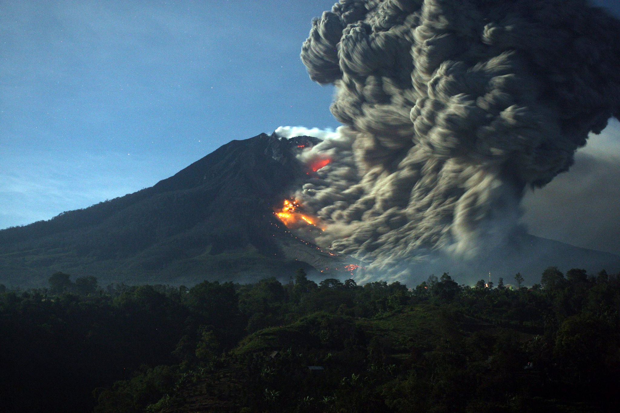 Mount Sinabung eruption...epa04437808 Mount Sinabung spews hot lava and volcanic ash as it is seen from Karo, North Sumatra, Indonesia, 09 October 2014. Mount Sinabung erupted in the last four days, forcing hundreds of people to flee their home. The 2,460-metre volcano had been dormant for 400 years before it erupted in August 2010.  EPA/DEDY SAHPUTRA