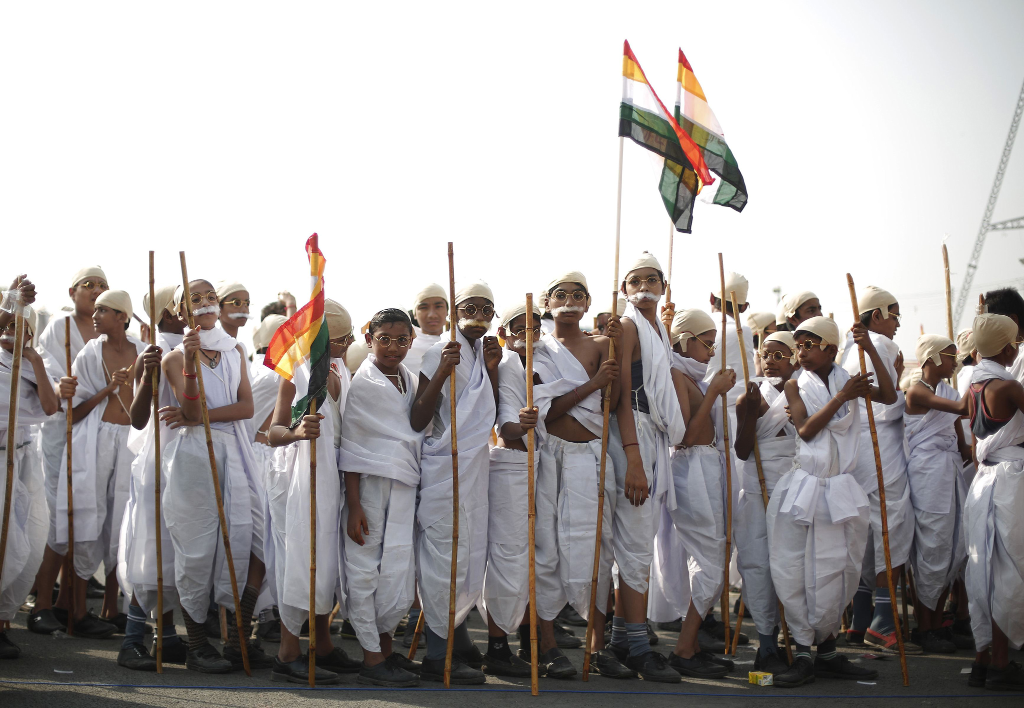 School children dressed as Mahatma Gandhi take part in a march to mark the 145th birth anniversary of Gandhi in New Delhi