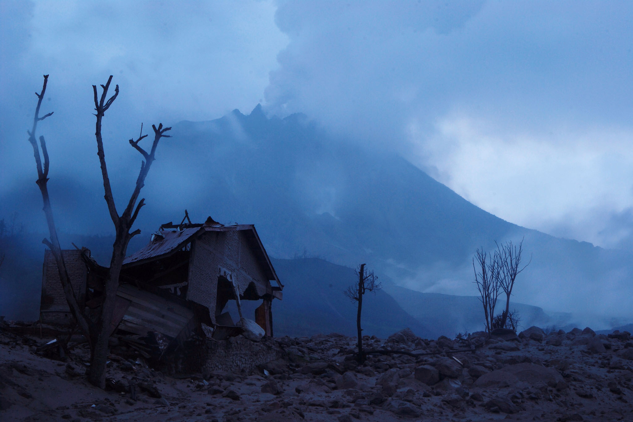 TOPSHOTS In this photograph taken on Oct...TOPSHOTS In this photograph taken on October 30, 2014, a house is in ruins and partly buried by volcanic ash and lava from the eruption of Mount Sinabung volcano seen in the background, as seen from the abandoned Sukameriah village in Karo district located in the volcano's danger zone. Indonesian President Joko Widodo ordered authorities to speed up the relocation of displaced residents during his visit at the evacuation center in Karo district in Sumatra island on October 29, 2014. Sinabung began erupting on September 2013 and in February 2014 an eruption killed about 17 people while more than 33,000 residents were forced to flee their homes.  AFP PHOTO / SUTANTA ADITYASUTANTA ADITYA/AFP/Getty Images