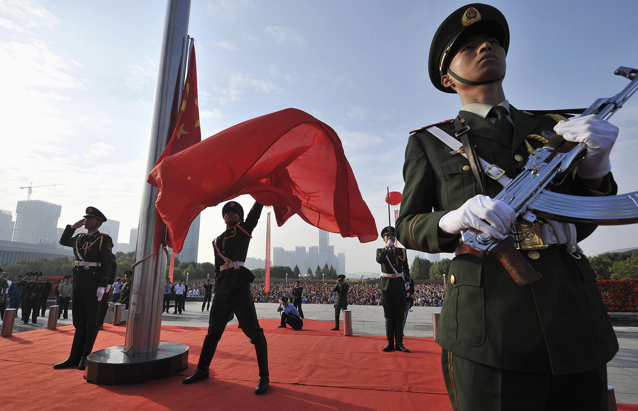 A paramilitary policeman spreads a Chinese national flag during a flag-raising ceremony to mark the 65th anniversary of the founding of the People's Republic of China, in Hefei