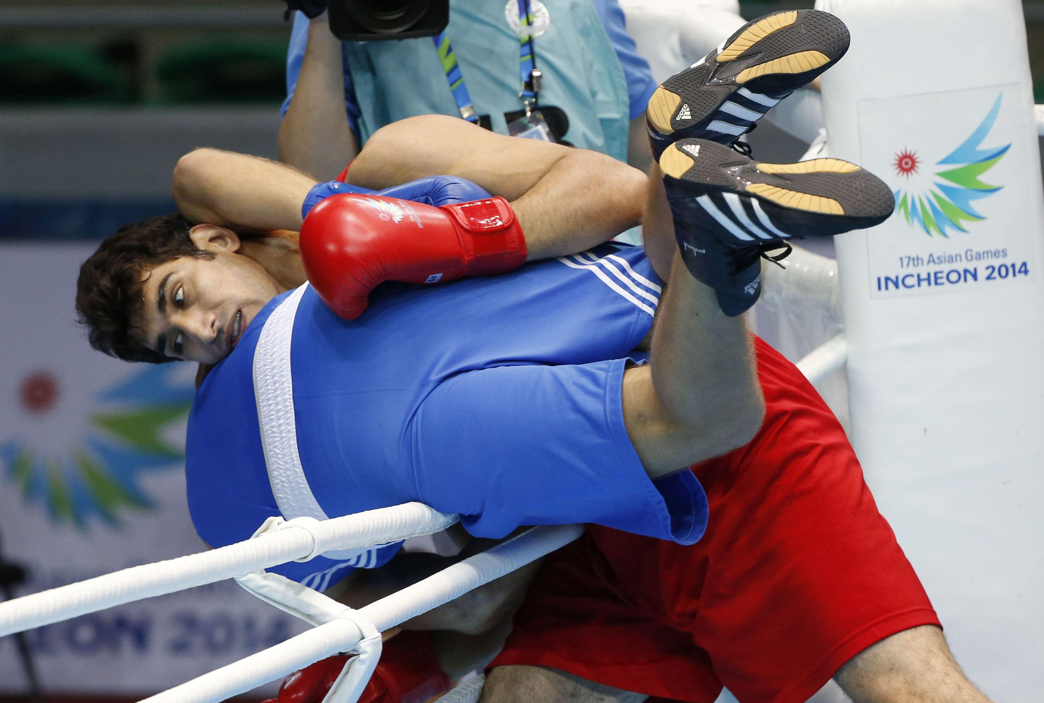 Kazakhstan's Anton Pinchuk is almost lifted out of the ring by Iran's Ali Mazaheri during their men's gold medal heavyweight 91kg boxing match at the Seonhak Gymnasium during the 2014 Asian Games in Incheon