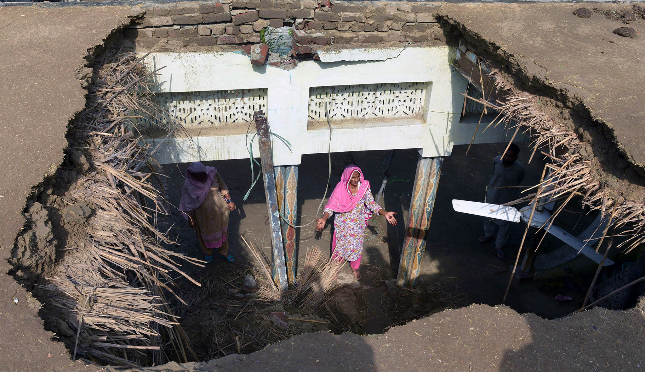 A Pakistani woman gestures beneath the damaged roof of her house