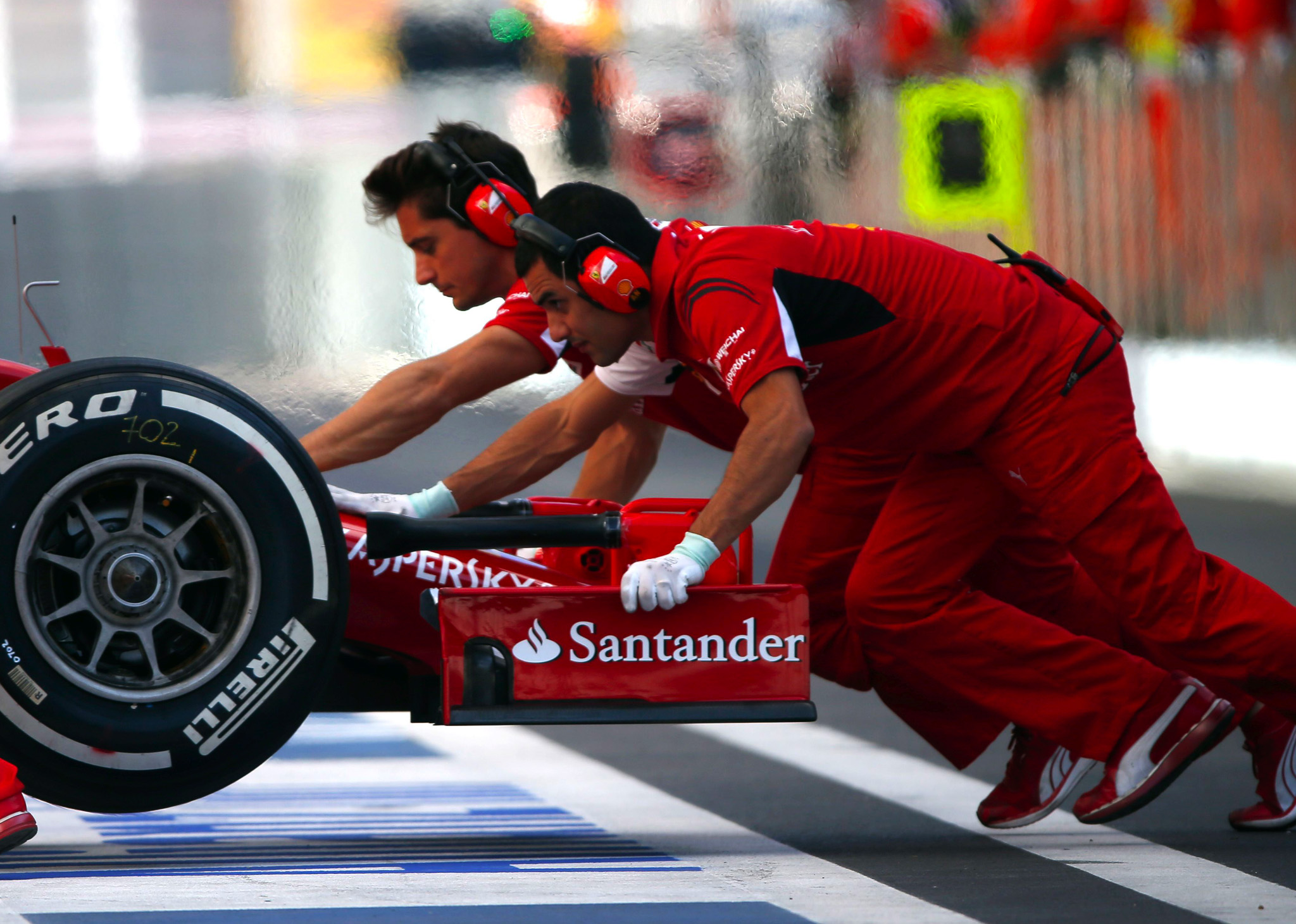 Ferrari Formula One mechanics push the car of Kimi Raikkonen of Finland during the first free practice session of the Russian F1 Grand Prix in the Sochi Autodrom circuit.