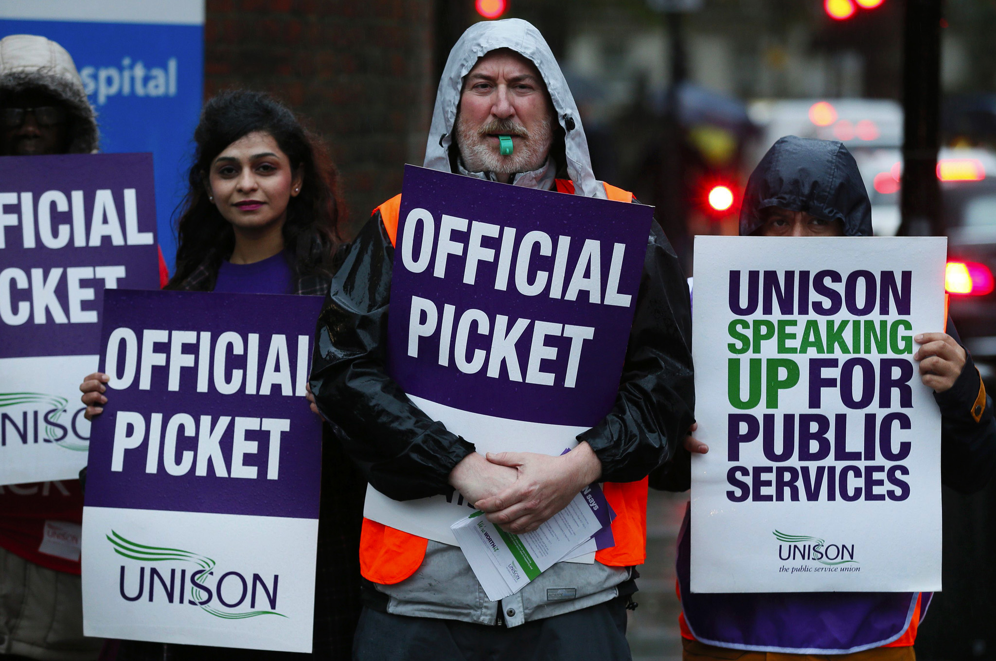 NHS workers hold placards during a strike, outside St Pancras Hospital in London. Thousands of health workers in Britain went on strike on Monday to protest against a pay freeze, the first walk out over pay in the country's state-run National Health Service (NHS) for over thirty years.
