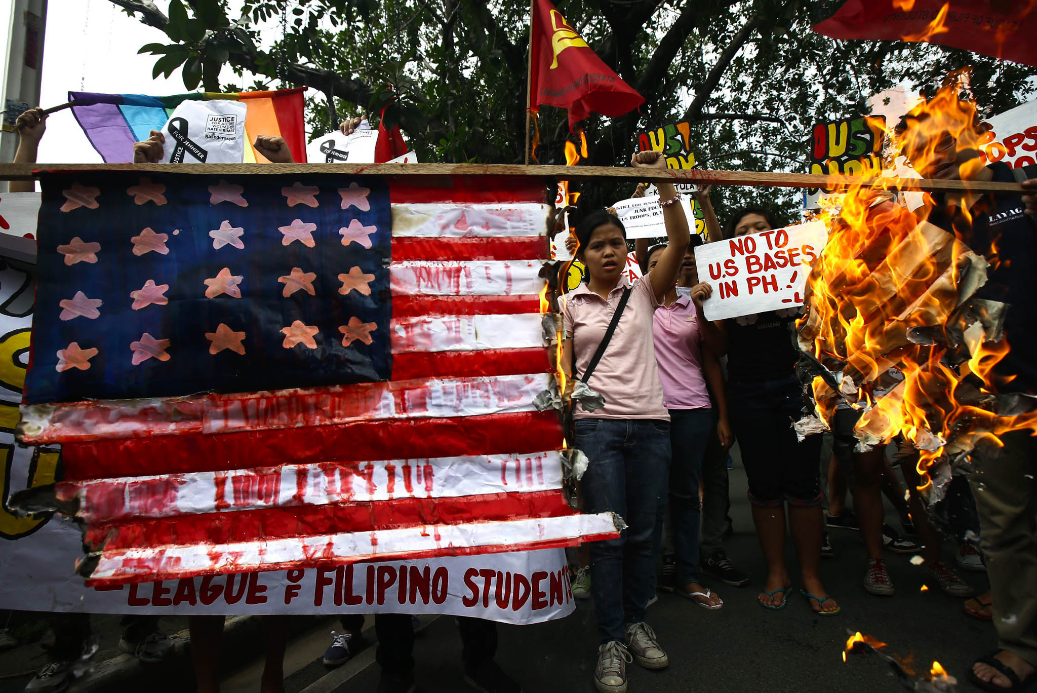 Filipino student protesters burn a mock US flag during a rally outside the US embassy in Manila. The group stormed the US embassy demanding to hand over a US Marine who allegedly killed a transgender person in northern Philippines.