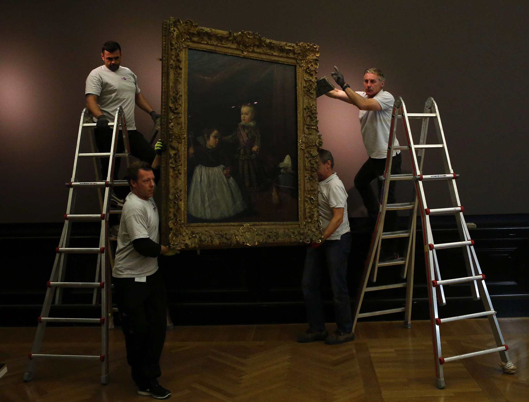 "Employees of Vienna's Art History Museum (Kunsthistorisches Museum Wien) adjust the painting ""Infant Balthasar Charles with a Dwarf"" by Spanish artist Diego Velazquez, prior to the opening of the major exhibition ""Velazquez"" in Vienna."