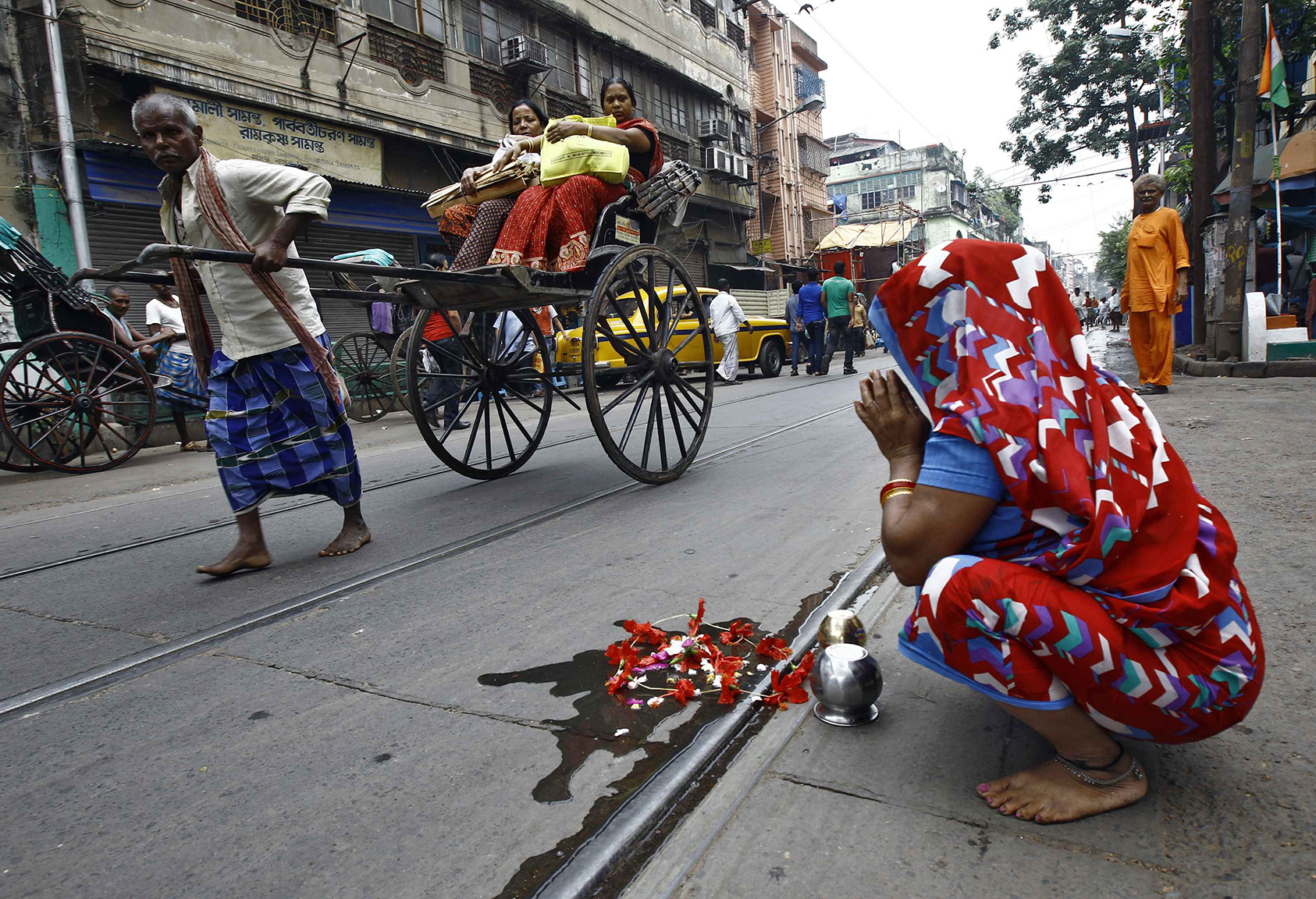 A woman offers prayers by a road as a rickshaw puller transports passengers in Kolkata