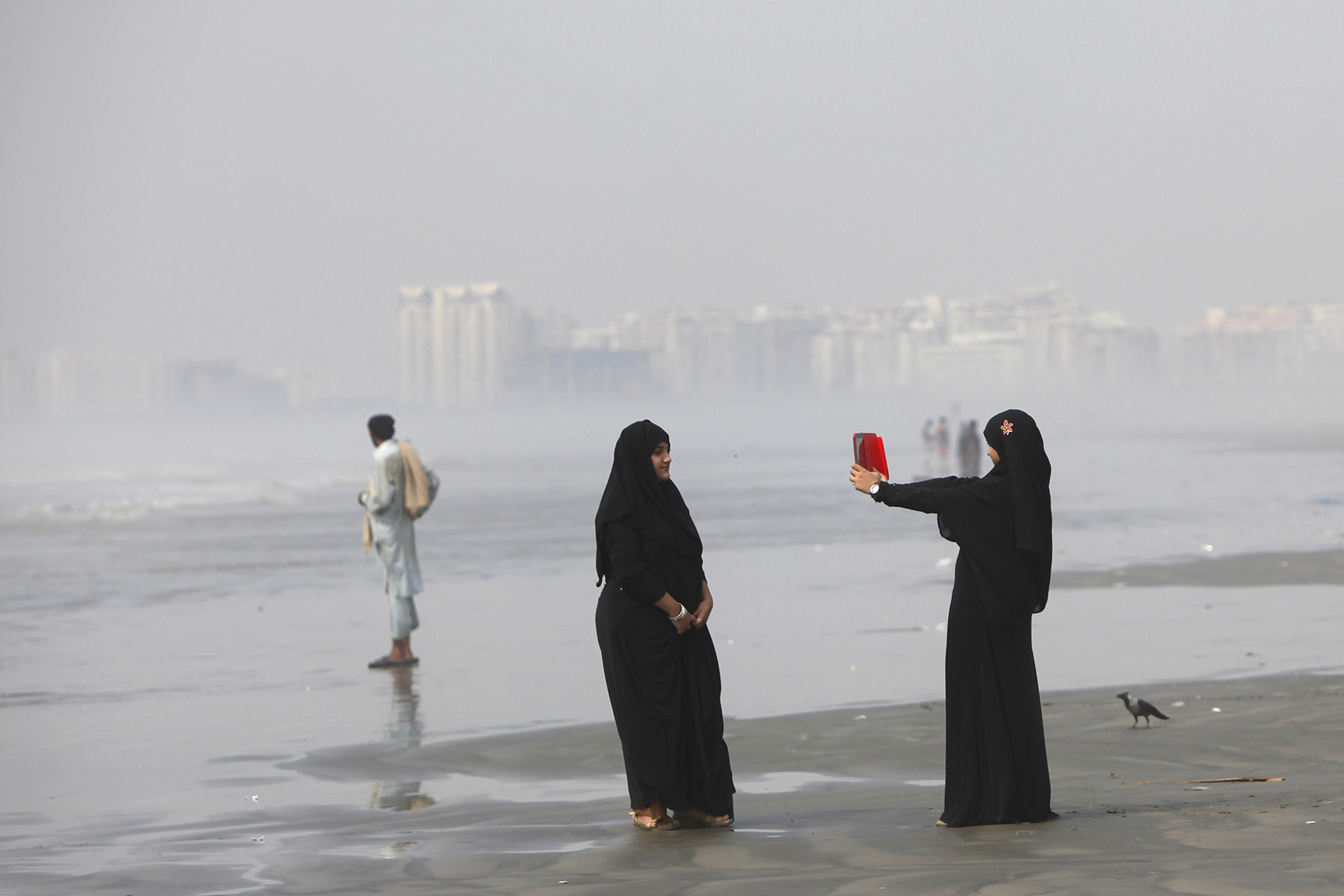 Girls clad in burqas take picture with a tablet while visiting Karachi's Clifton beach