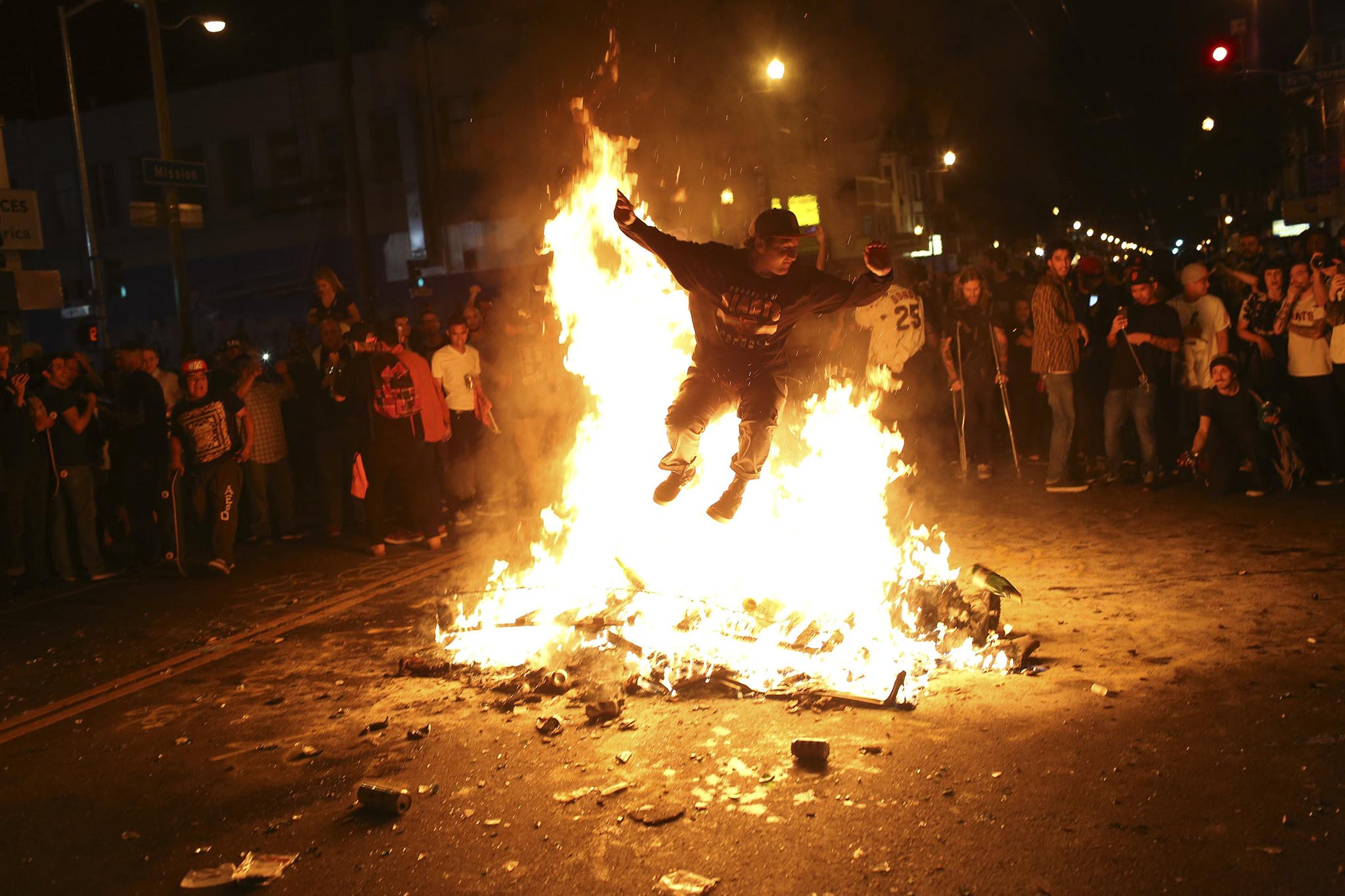 A man jumps through a fire along a street in the Mission District during a celebration after the San Francisco Giants defeated the Kansas City Royals in Game 7 of the World Series, in San Francisco, California