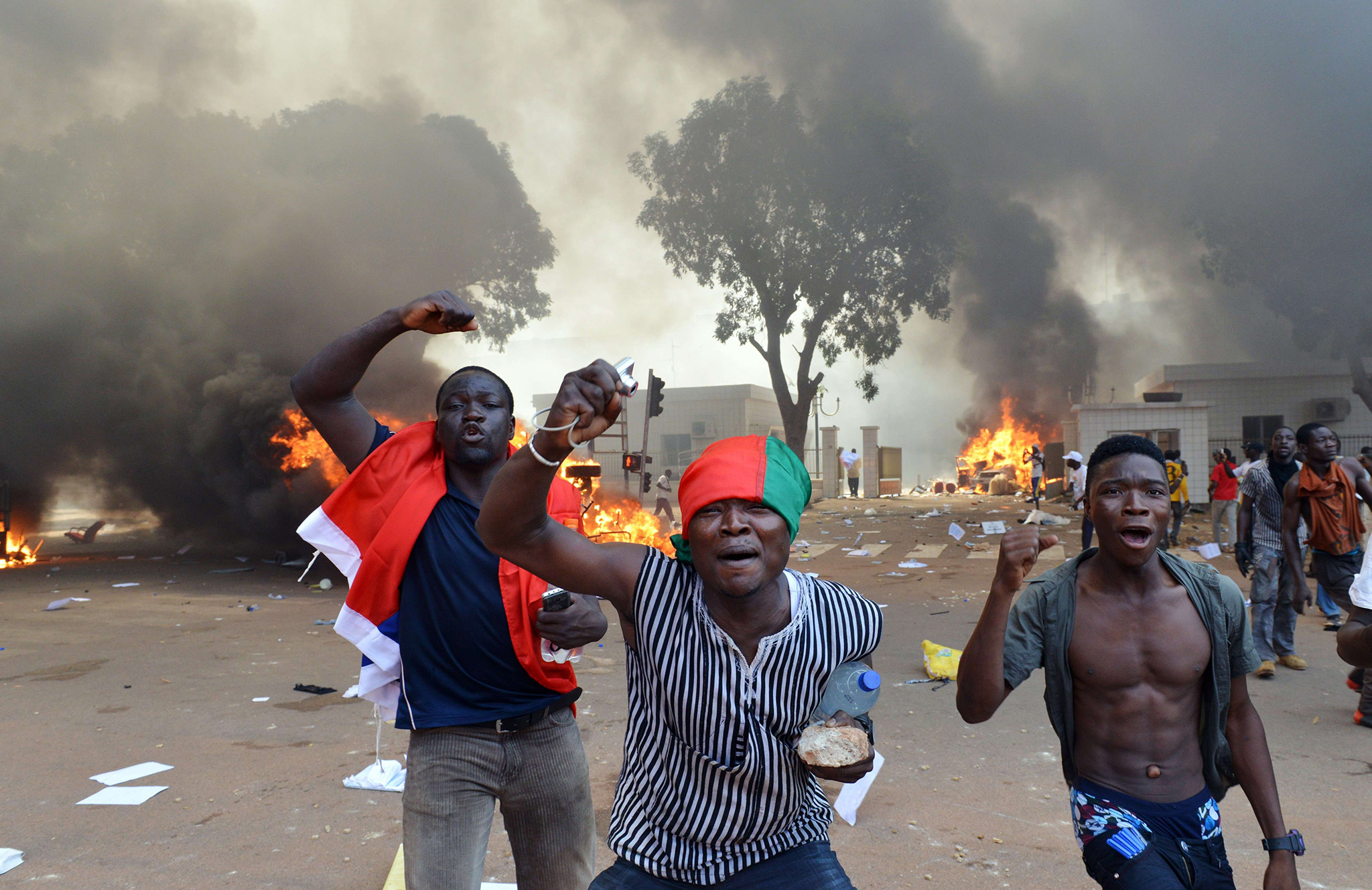 Men shout slogans in front of burning cars, near the Burkina Faso's Parliament where demonstrators set fire, on October 30, 2014 in Ouagadougou, as they protest against plans to change the constitution to allow President Blaise Compaore to extend his 27-year rule. Police had fired tear gas on protesters to try to prevent them from moving in on the National Assembly building in the capital Ouagadougou ahead of a vote on the controversial legislation. But about 1,500 people managed to break through the security cordon and were ransacking parliament, according to AFP correspondents. Protesters ransacked offices, setting fire to documents and stealing computer equipment, and set fire to cars outside. AFP PHOTO / ISSOUF SANOGOISSOUF SANOGO/AFP/Getty Images