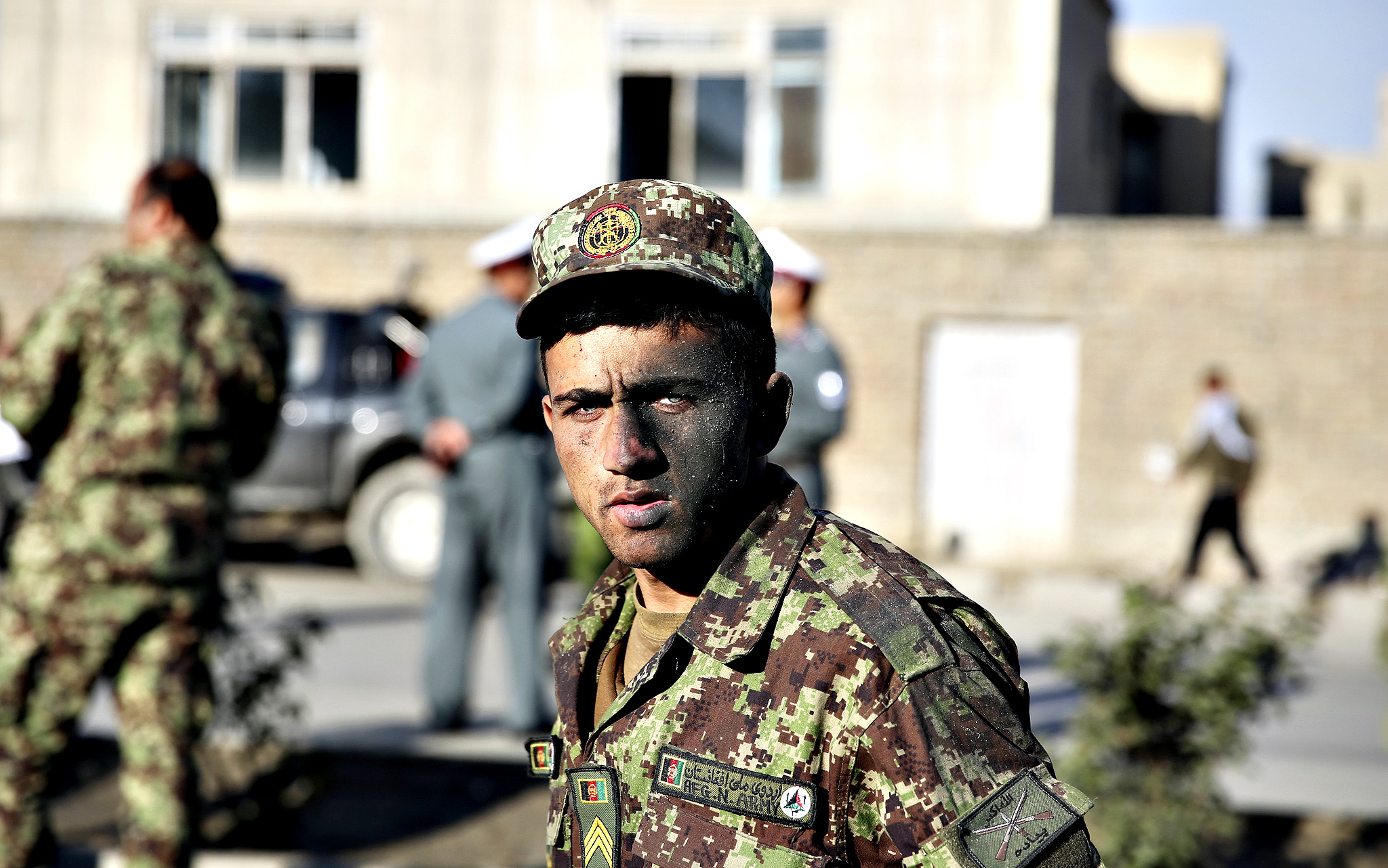 An Afghan National Army soldger who survived a road side bomb explosion, walks by the site of the blast in Kabul, Afghanistan, Tuesday, Oct. 21, 2014. At least four Afghan soldiers have been killed in the attack in the capital.