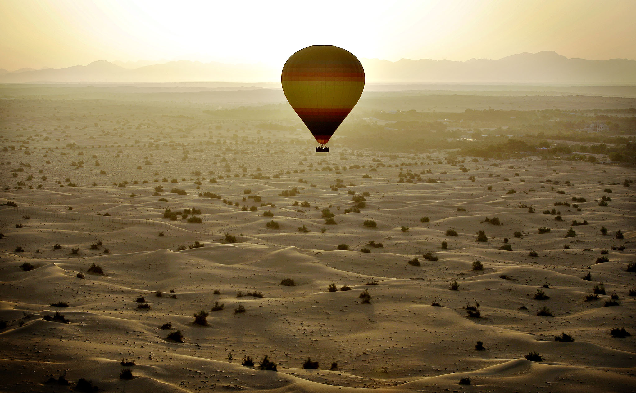 The sun rises from behind the Hajjar Mountains as one of the world largest hot air balloons carries 24 passengers flying over the Margham desert about 60 km (37 miles) southeast of Dubai, United Arab Emirates
