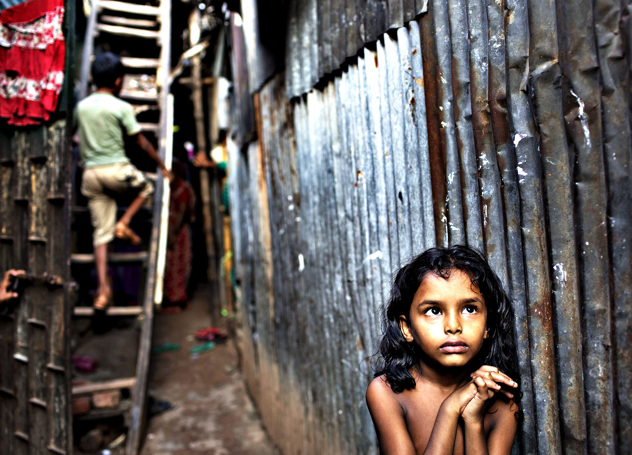 A Bangladeshi child stands in an alley as a boy climbs a ladder outside their home at a slum in Dhaka, Bangladesh, Friday, Oct. 17, 2014. The International Day for the Eradication of Poverty is observed on October 17 and is designated to promote awareness of the need to eradicate poverty and destitution in all countries.