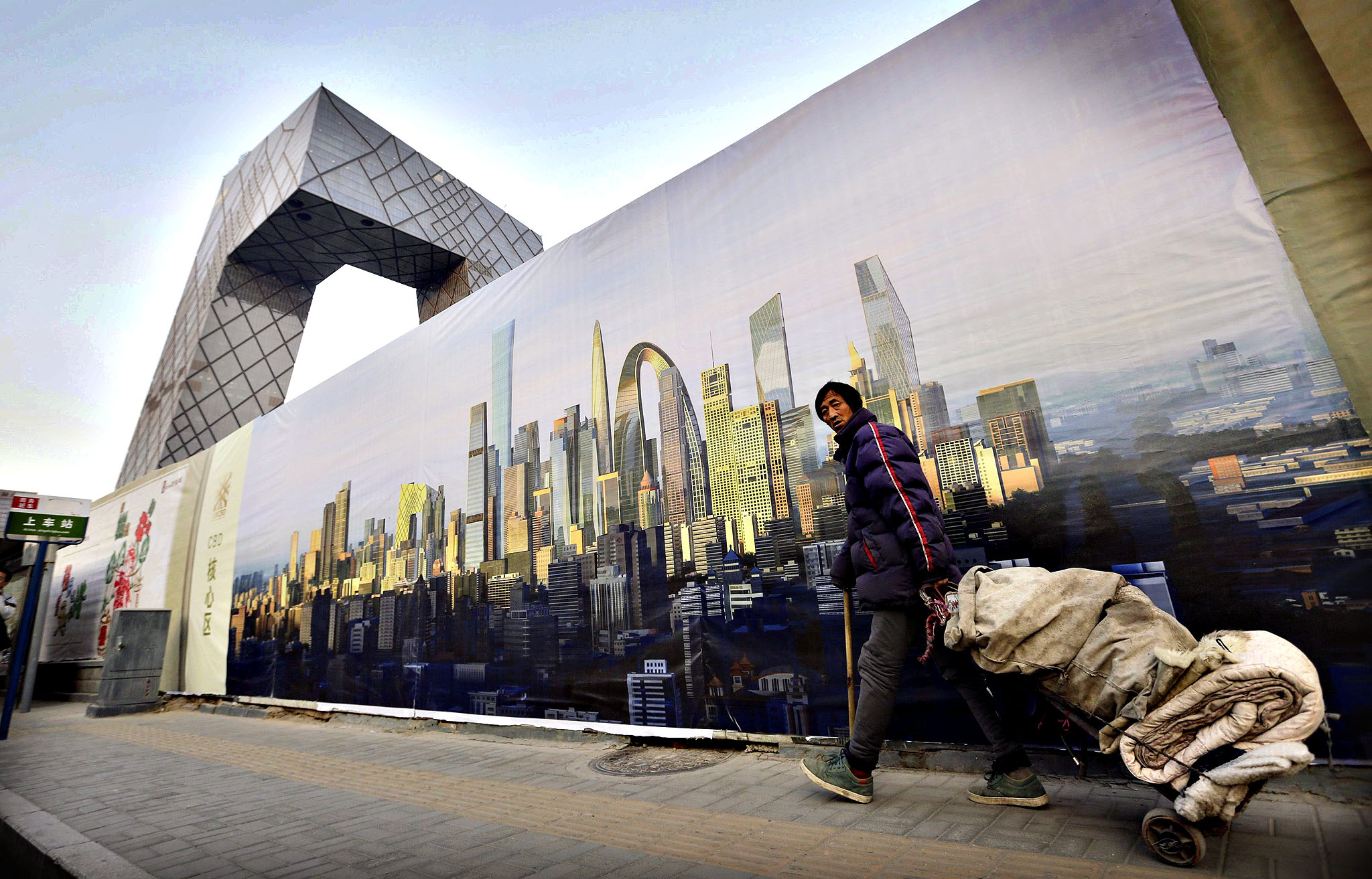 A ragpicker walks past a poster showing Beijing's central business district, next to the CCTV building in Beijing...A ragpicker walks past a poster showing Beijing's central business district next to the China Central Television (CCTV) building outside a construction site in Beijing, October 21, 2014. It is still taking time for reform measures to gain traction, Chinese Premier Li Keqiang was quoted as saying by the Foreign Ministry.