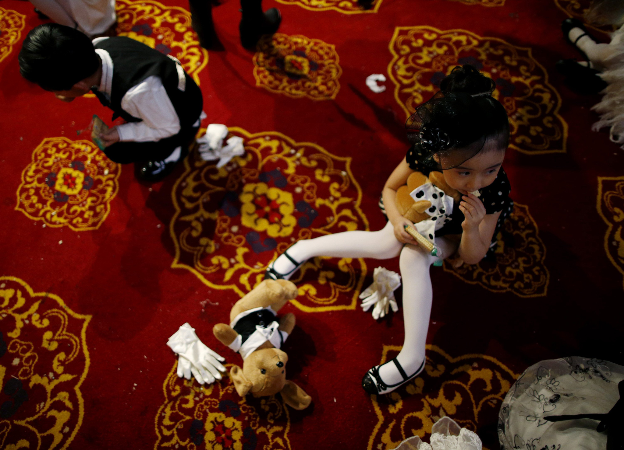 A child model eats a biscuit on the floor of the backstage during a rehearsal for the Dong Wenmei T100 Children's Collection during China Fashion Week in Beijing
