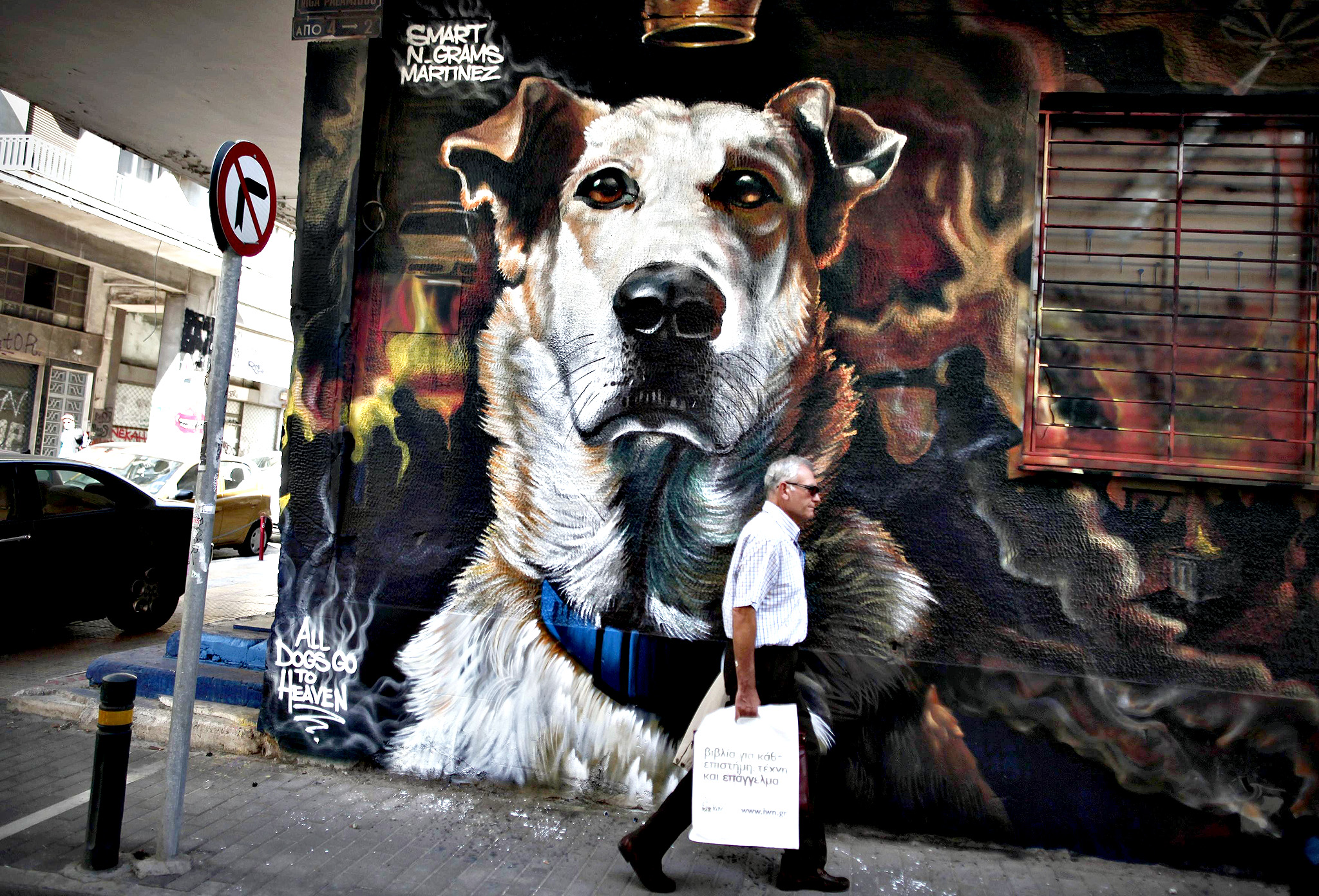 "A man walks past a graffiti of Sausage, a stray dog, painted by street artists Smart, N_Grams and Martinez in Athens October 20, 2014. The ginger mongrel called ""Loukanikos"" in Greek, who became famous for appearing at anti-austerity protests and barking at riot police at the height of Greece's debt crisis, has died of a heart attack, local officials said on October 9, 2014."